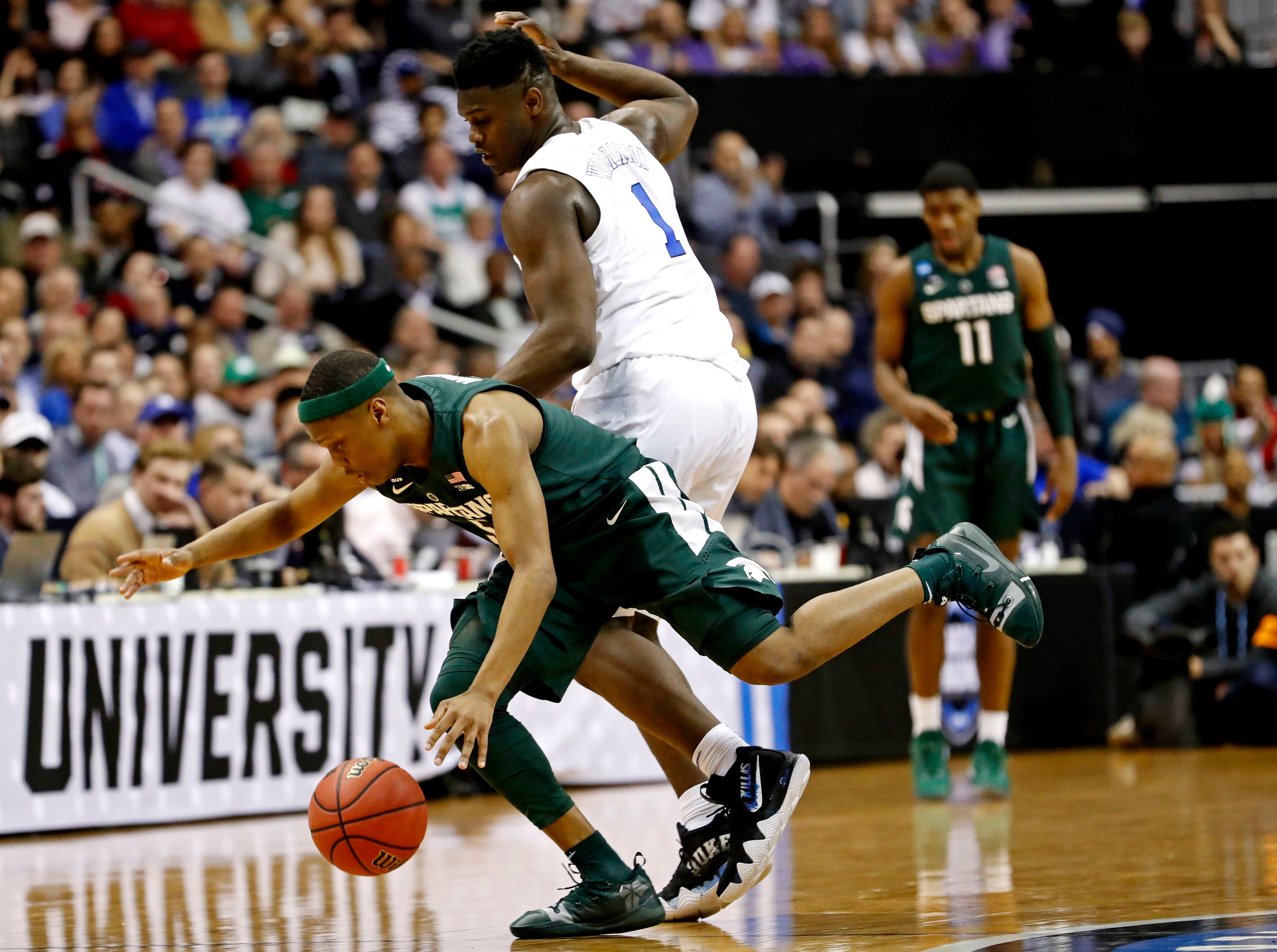 Mar 31, 2019; Washington, DC, USA; Duke Blue Devils forward Zion Williamson (1) and Michigan State Spartans guard Cassius Winston (5) go for a loose ball during the first half in the championship game of the east regional of the 2019 NCAA Tournament at Capital One Arena. Mandatory Credit: Geoff Burke-USA TODAY Sports