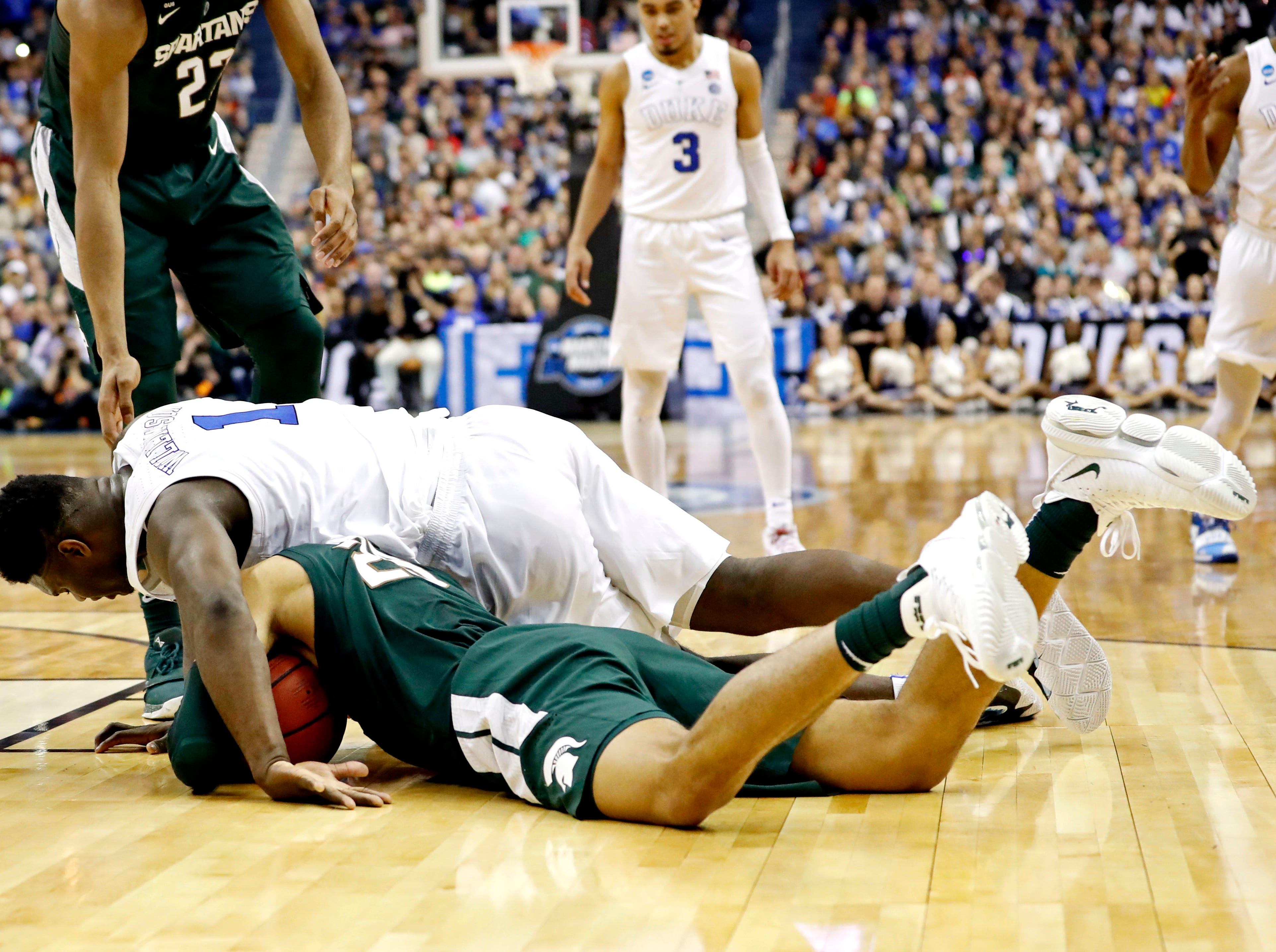 Mar 31, 2019; Washington, DC, USA; Duke Blue Devils forward Zion Williamson (1) and Michigan State Spartans forward Xavier Tillman (23) go for a loose ball during the first half in the championship game of the east regional of the 2019 NCAA Tournament at Capital One Arena. Mandatory Credit: Geoff Burke-USA TODAY Sports