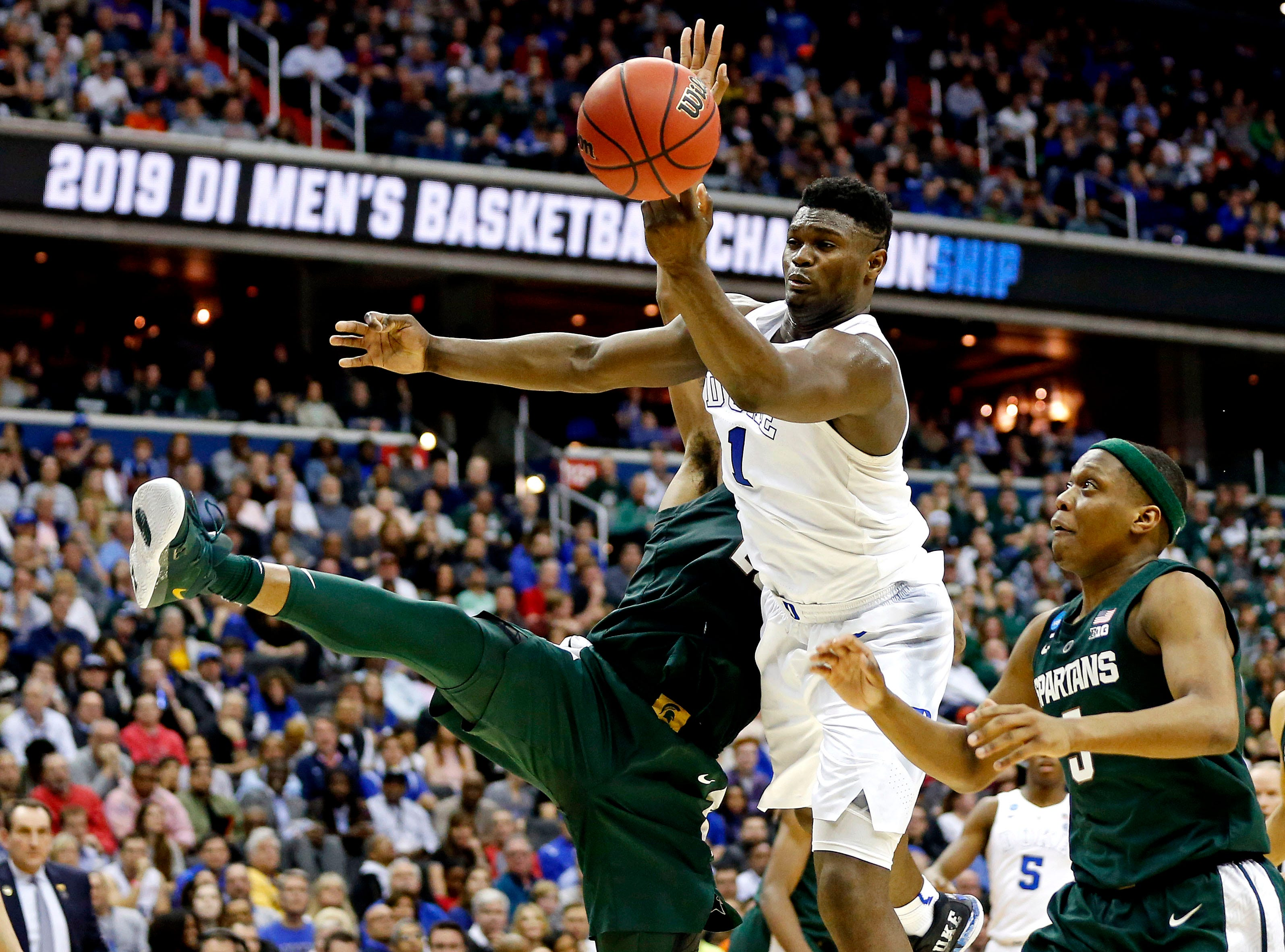 Mar 31, 2019; Washington, DC, USA; Duke Blue Devils forward Zion Williamson (1) goes for a reboot against Michigan State Spartans guard Cassius Winston (5) and forward Xavier Tillman (23) during the second half in the championship game of the east regional of the 2019 NCAA Tournament at Capital One Arena. Mandatory Credit: Amber Searls-USA TODAY Sports