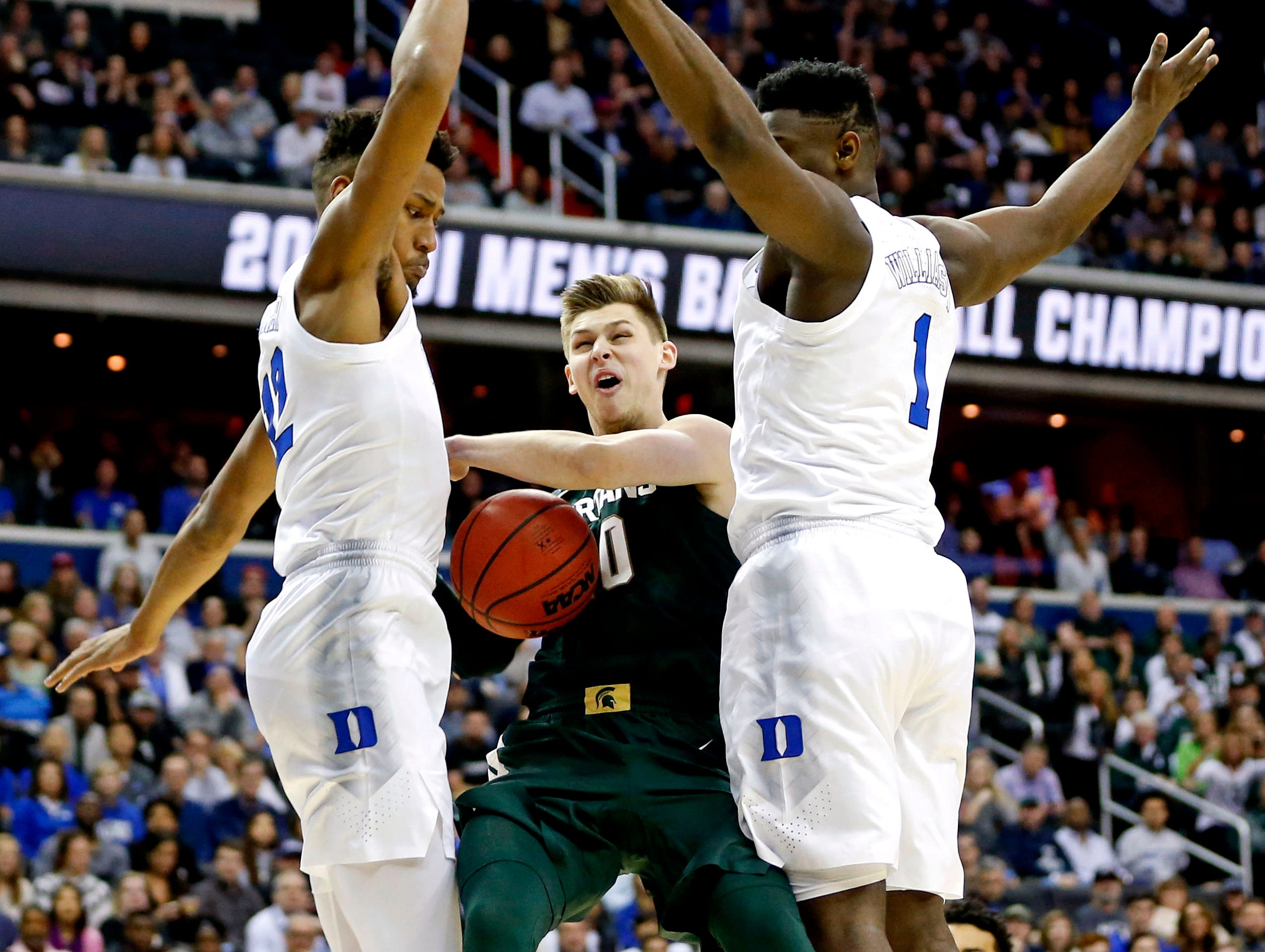 Michigan State Spartans guard Matt McQuaid (20) drives to the basket against Duke Blue Devils forward Zion Williamson (1) during the first half in the championship game of the east regional of the 2019 NCAA Tournament at Capital One Arena.