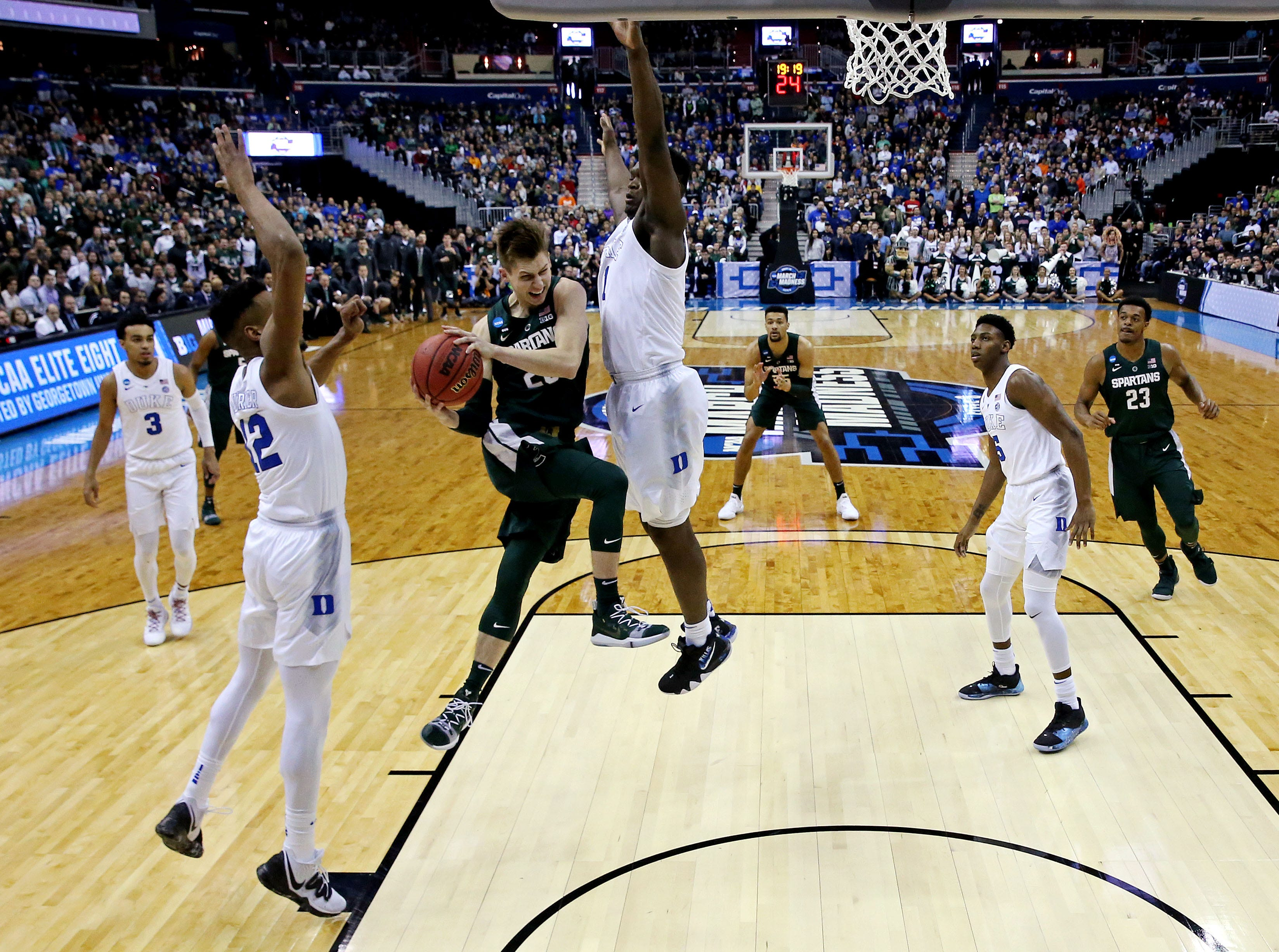 Mar 31, 2019; Washington, DC, USA; Michigan State Spartans guard Matt McQuaid (20) drives to the basket against Duke Blue Devils forward Zion Williamson (1) and forward Javin DeLaurier (12) during the first half in the championship game of the east regional of the 2019 NCAA Tournament at Capital One Arena. Mandatory Credit: Geoff Burke-USA TODAY Sports