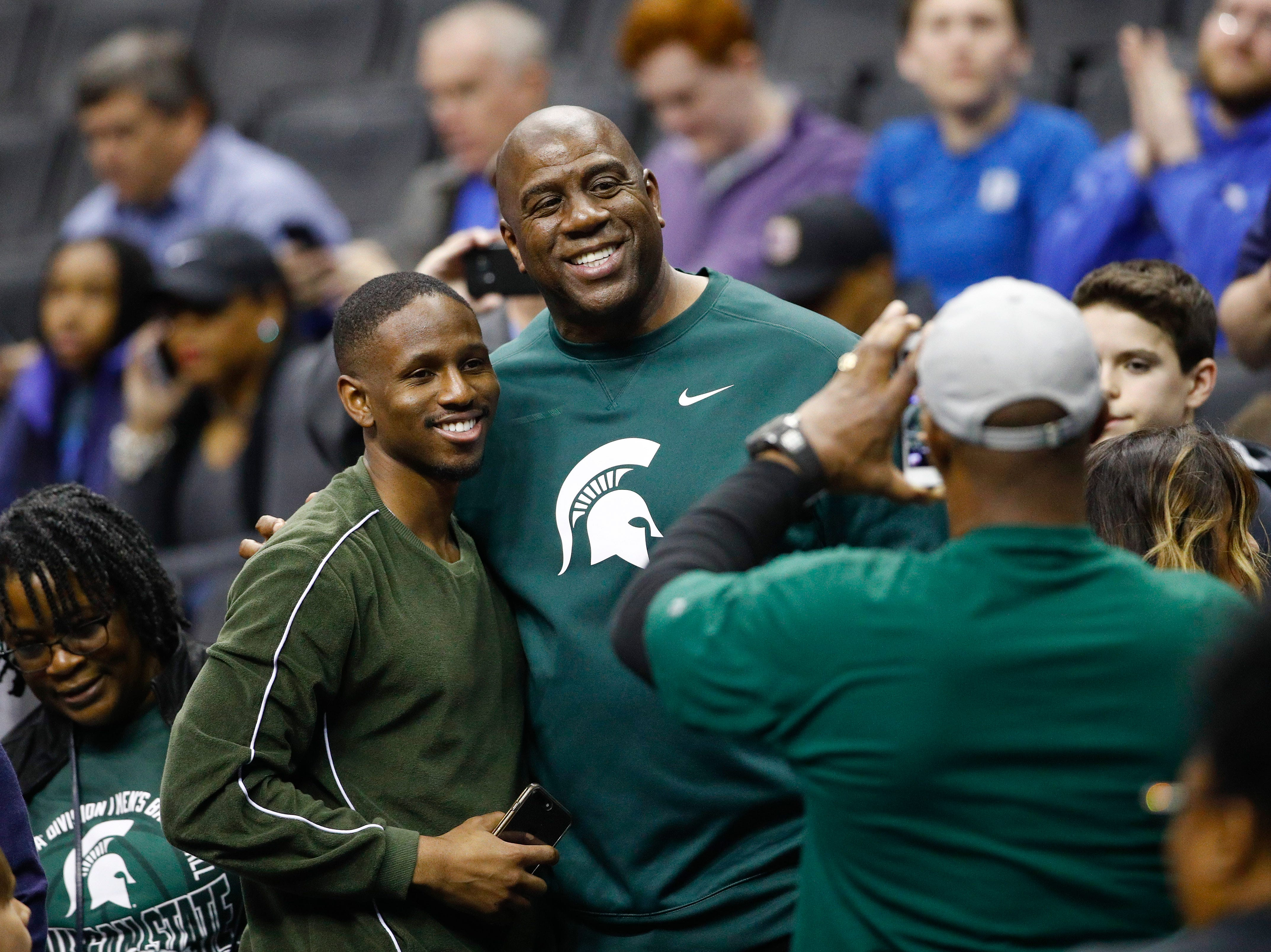 Los Angeles Lakers president and Michigan State alumni Magic Johnson, center, poses for photos before the start of a NCAA men's East Regional final college basketball game between Michigan State and Duke in Washington, Sunday, March 31, 2019.