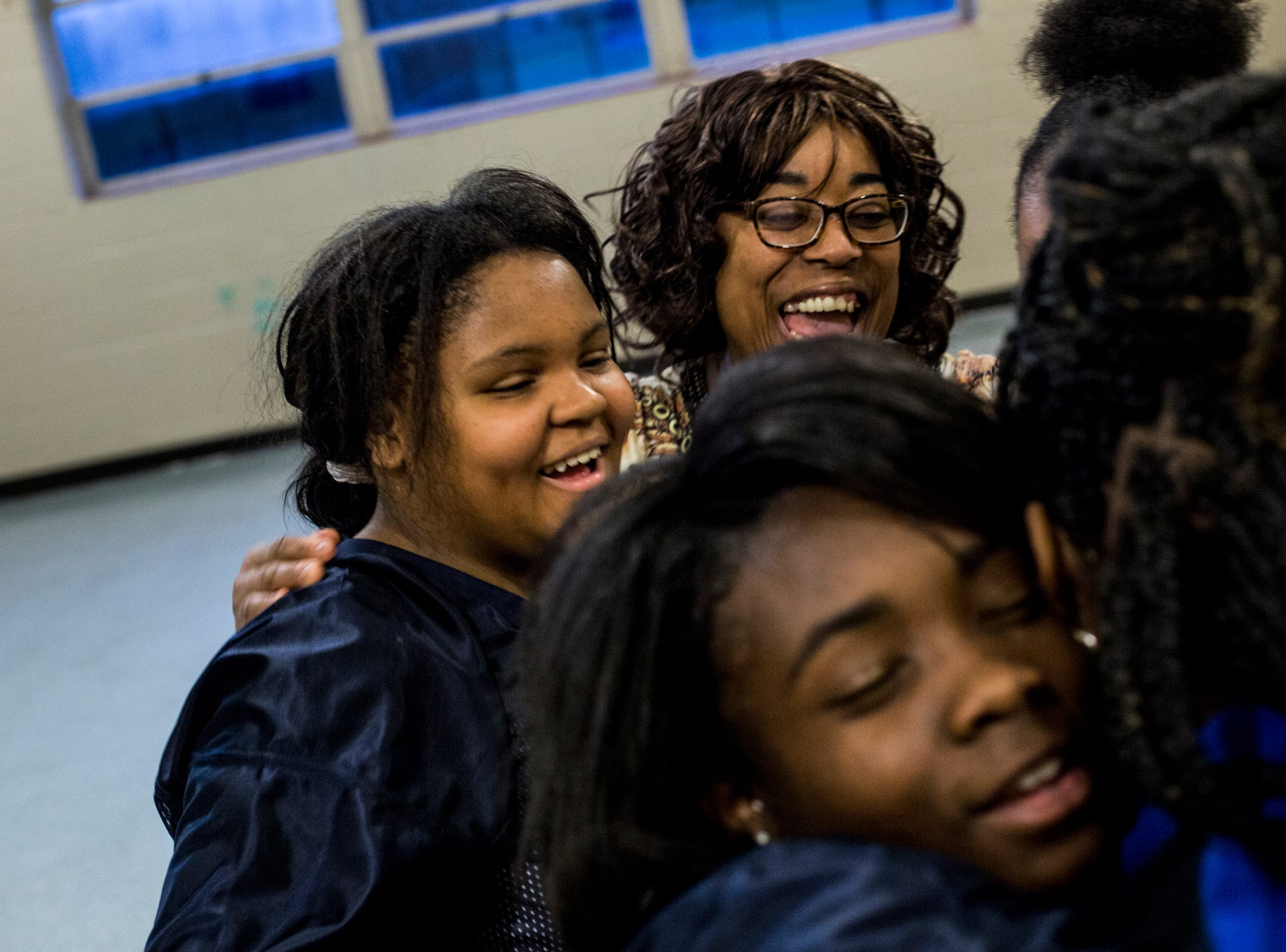 Volunteer coach Sharon Cole, top right, embraces members of the Memphis Community Youth Mighty Marchers after a practice at the Ed Rice Community Center in Frayser on March 28, 2019.