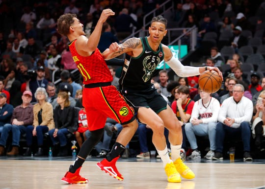 Bucks forward D.J. Wilson (right) is called for an offensive foul against Hawks guard Trae Young in the first half Sunday.