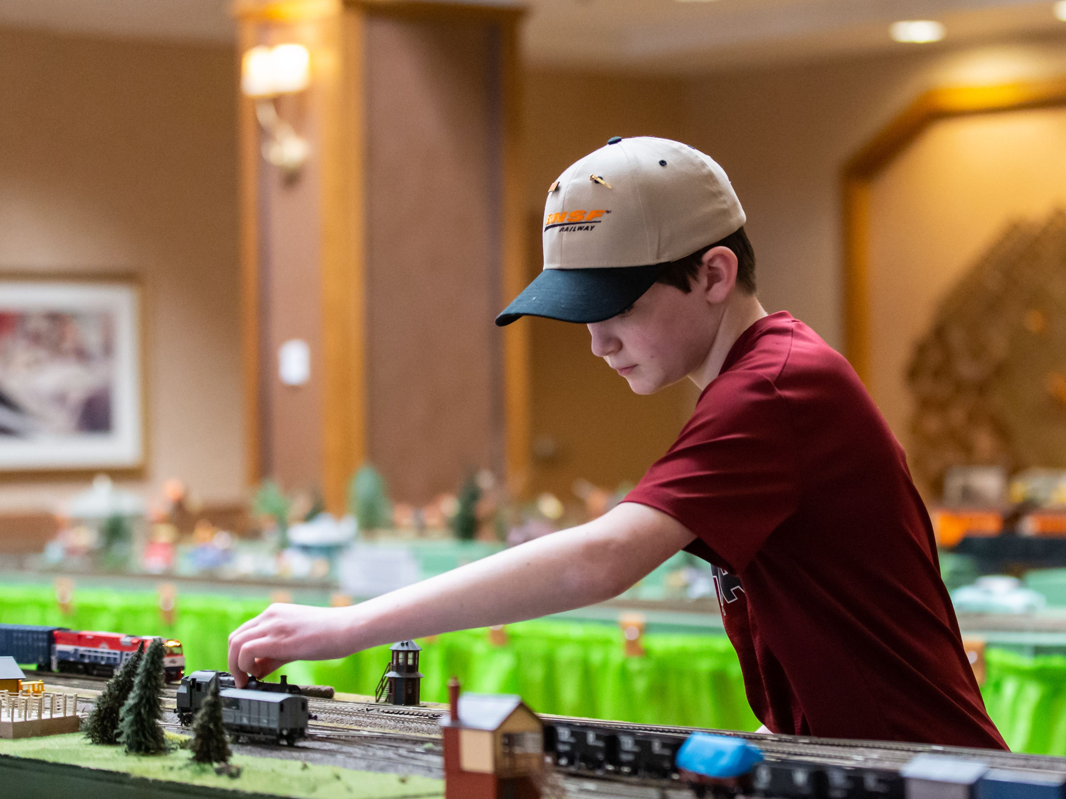 River Avram, 11, of Ixonia helps position a locomotive during the Trains, Tracks and Switches exhibit at Shorehaven Health and Rehabilitation Center in Oconomowoc on Thursday, March 28, 2019.