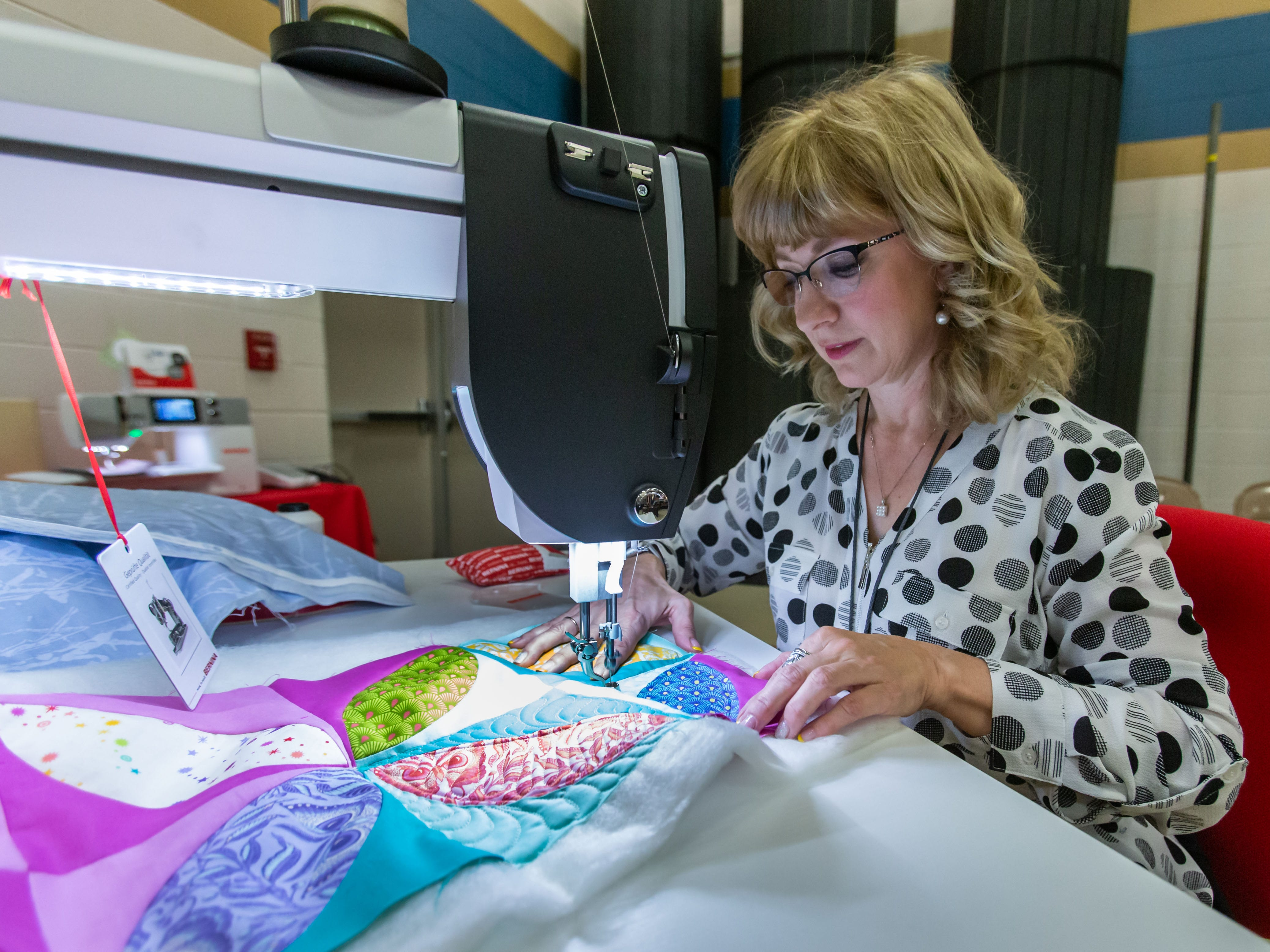 Employee Donna Bularz of Bigsby's Sewing Center in Elm Grove demonstrates free motion quilting during the Mukwonago Crazy Quilters 32nd annual Quilt Show at Park View Middle School on Saturday, March 30, 2019. The popular two-day event features show quilts, demonstrations, vendors, raffles, appraisals and more.
