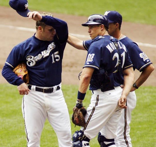 Ben Sheets talks with catcher Chad Moeller and pitching coach Mike Maddux in the fifth inning June 13, 2004, two innings after his nine-pitch, three-out performance.