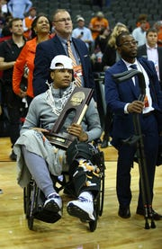 Injured Auburn player Chuma Okeke sits with his team's trophy after the Tigers beat UK.