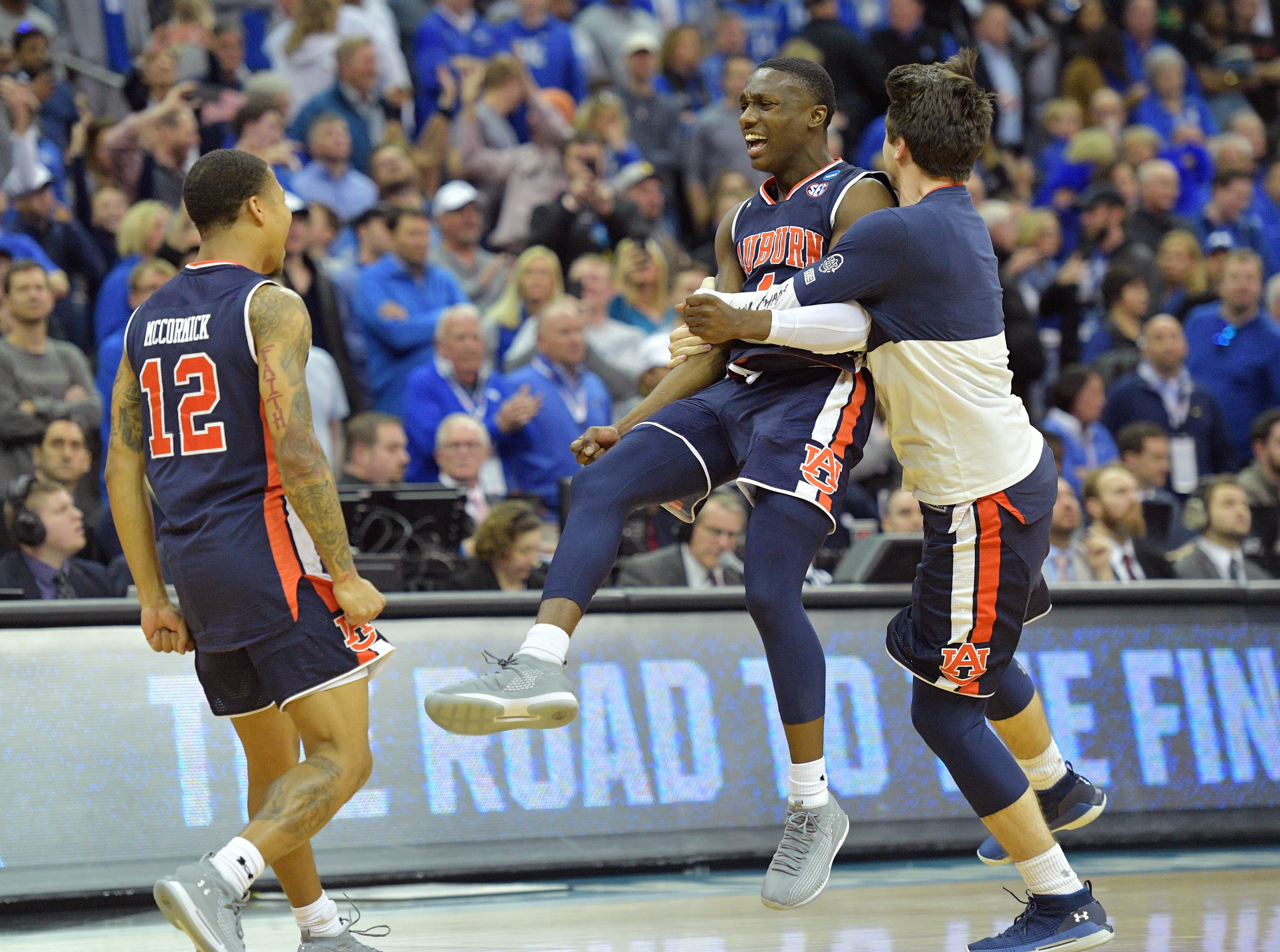 Mar 31, 2019; Kansas City, MO, United States; Auburn Tigers players including Jared Harper (1) and J'Von McCormick (12) celebrate after defeating the Kentucky Wildcats in the championship game of the midwest regional of the 2019 NCAA Tournament at Sprint Center. Mandatory Credit: Denny Medley-USA TODAY Sports