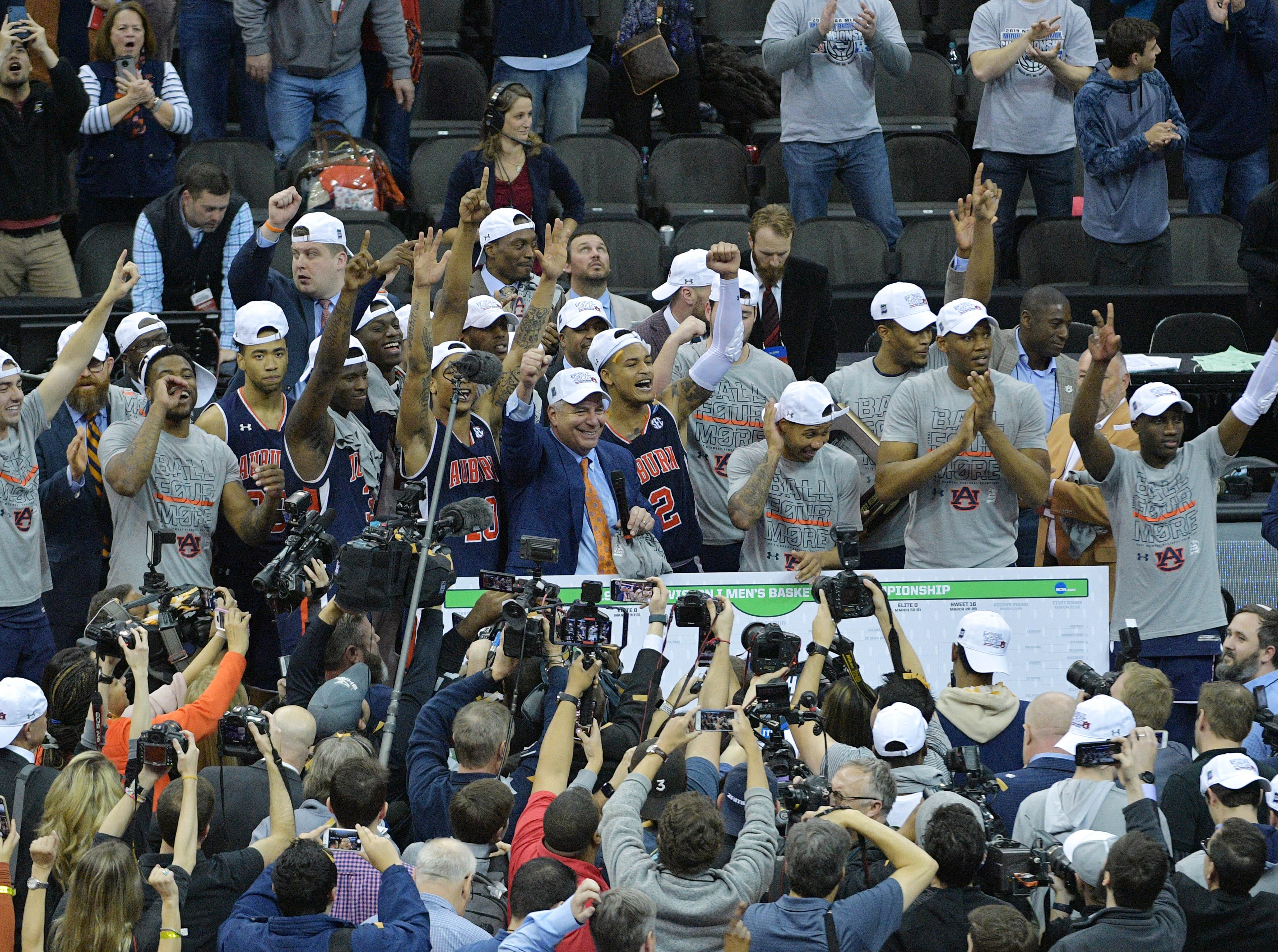 Mar 31, 2019; Kansas City, MO, United States; Auburn Tigers players and coach Bruce Peral celebrate after defeating the Kentucky Wildcats in the championship game of the midwest regional of the 2019 NCAA Tournament at Sprint Center. Mandatory Credit: Denny Medley-USA TODAY Sports
