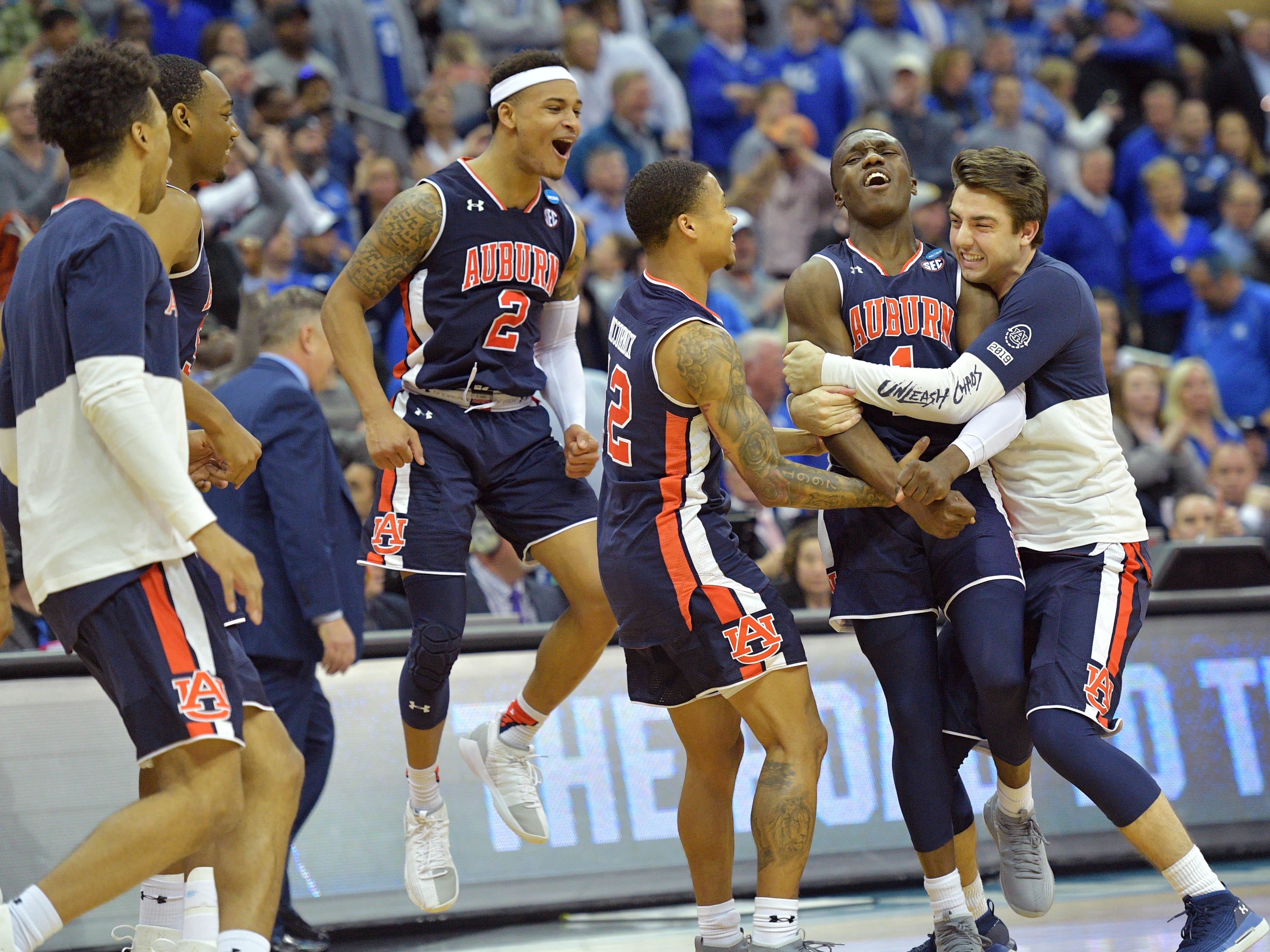 Auburn players including Jared Harper (1) , Bryce Brown (2) and J'Von McCormick (12) celebrate after defeating the Kentucky Wildcats in the championship game of the midwest regional of the 2019 NCAA Tournament at Sprint Center on March 31, 2019, in Kansas City.