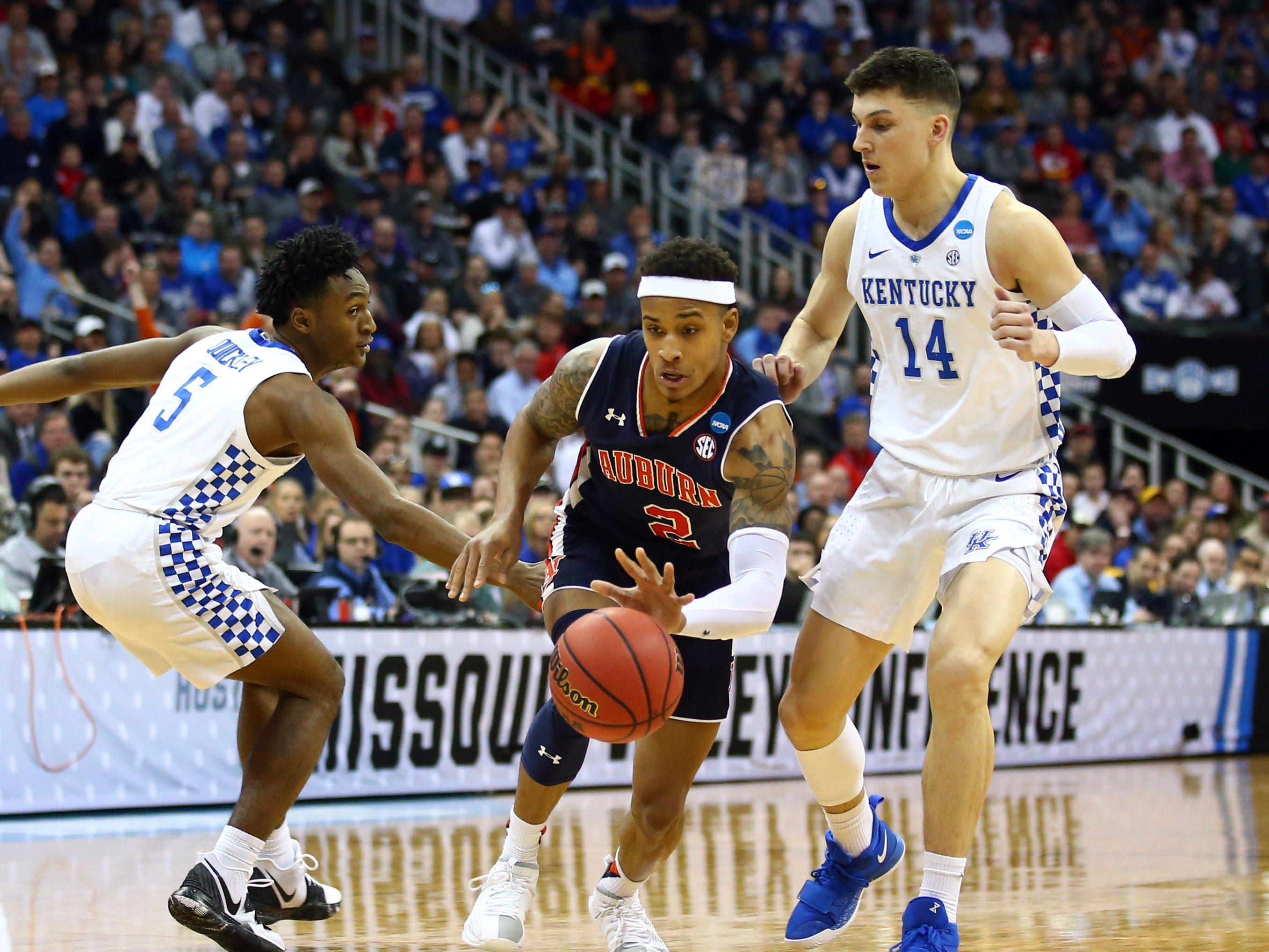 Mar 31, 2019; Kansas City, MO, United States; Auburn Tigers guard Bryce Brown (2) dribbles between Kentucky Wildcats guard Immanuel Quickley (5) and guard Tyler Herro (14) during the first half in the championship game of the midwest regional of the 2019 NCAA Tournament at Sprint Center. Mandatory Credit: Jay Biggerstaff-USA TODAY Sports