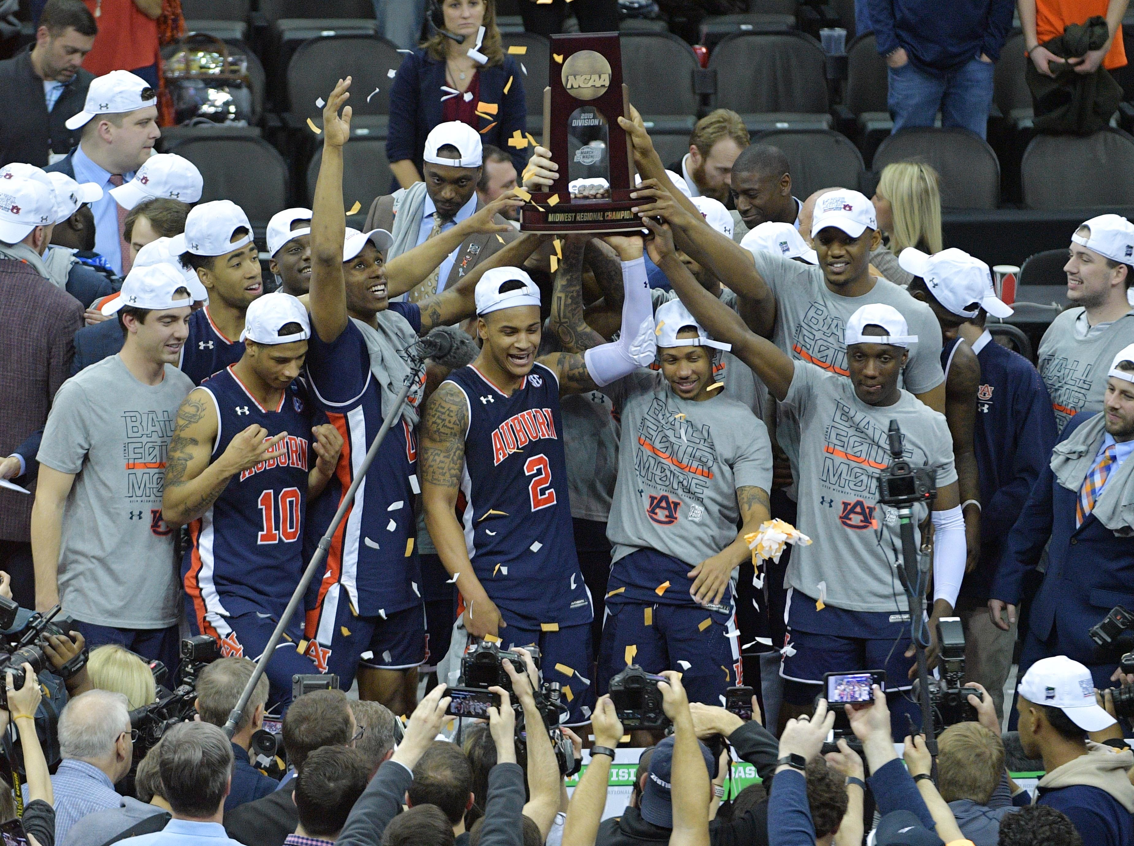 Mar 31, 2019; Kansas City, MO, United States; Auburn Tigers players celebrate with the trophy after defeating the Kentucky Wildcats in the championship game of the midwest regional of the 2019 NCAA Tournament at Sprint Center. Mandatory Credit: Denny Medley-USA TODAY Sports