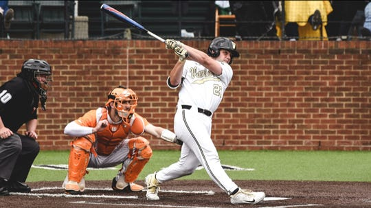 Vanderbilt's Ty Duvall hits a home run in the Commodores' win Saturday as Tennessee catcher Connor Pavolony looks on.