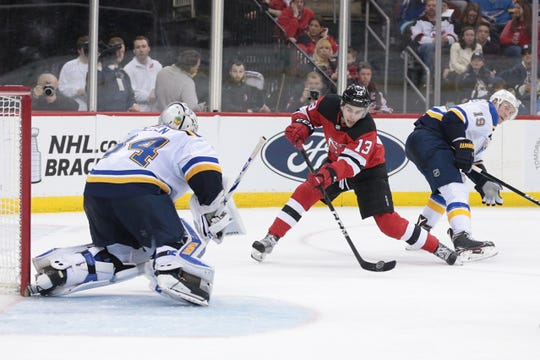 New Jersey Devils center Nico Hischier (13) shoots the puck at St. Louis Blues goaltender Jake Allen (34) in front of defenseman Jay Bouwmeester (19) during the second period at Prudential Center.