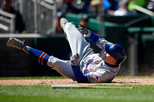 New York Mets' Brandon Nimmo tumbles as he scores on a double by Pete Alonso during the third inning of a baseball game against the Washington Nationals, Sunday, March 31, 2019, in Washington. (AP Photo/Nick Wass)