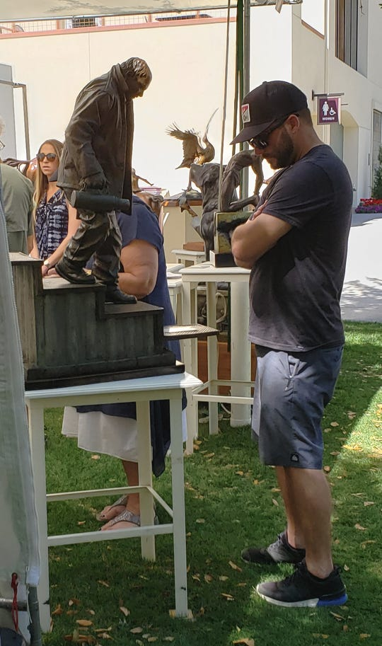 A visitor to the Indian Wells Arts Festival on Saturday, March 30, 2019, takes a closer look at a sculpture. The festival continues on Sunday, March 31, 2019.