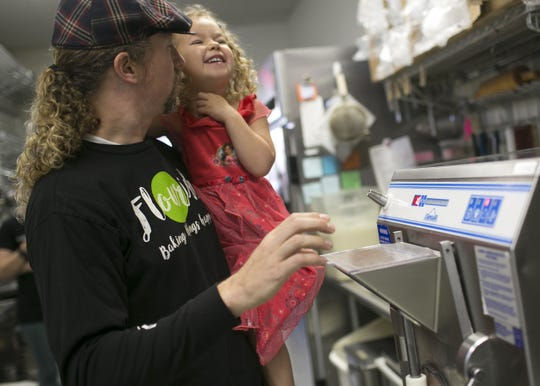 Cannabis cuisine chef Payton Curry holds his 4-year-old daughter Phionna Julep Curry while making CBD-infused gelato at Udder Delights in Gilbert, Ariz. on March 14, 2018.