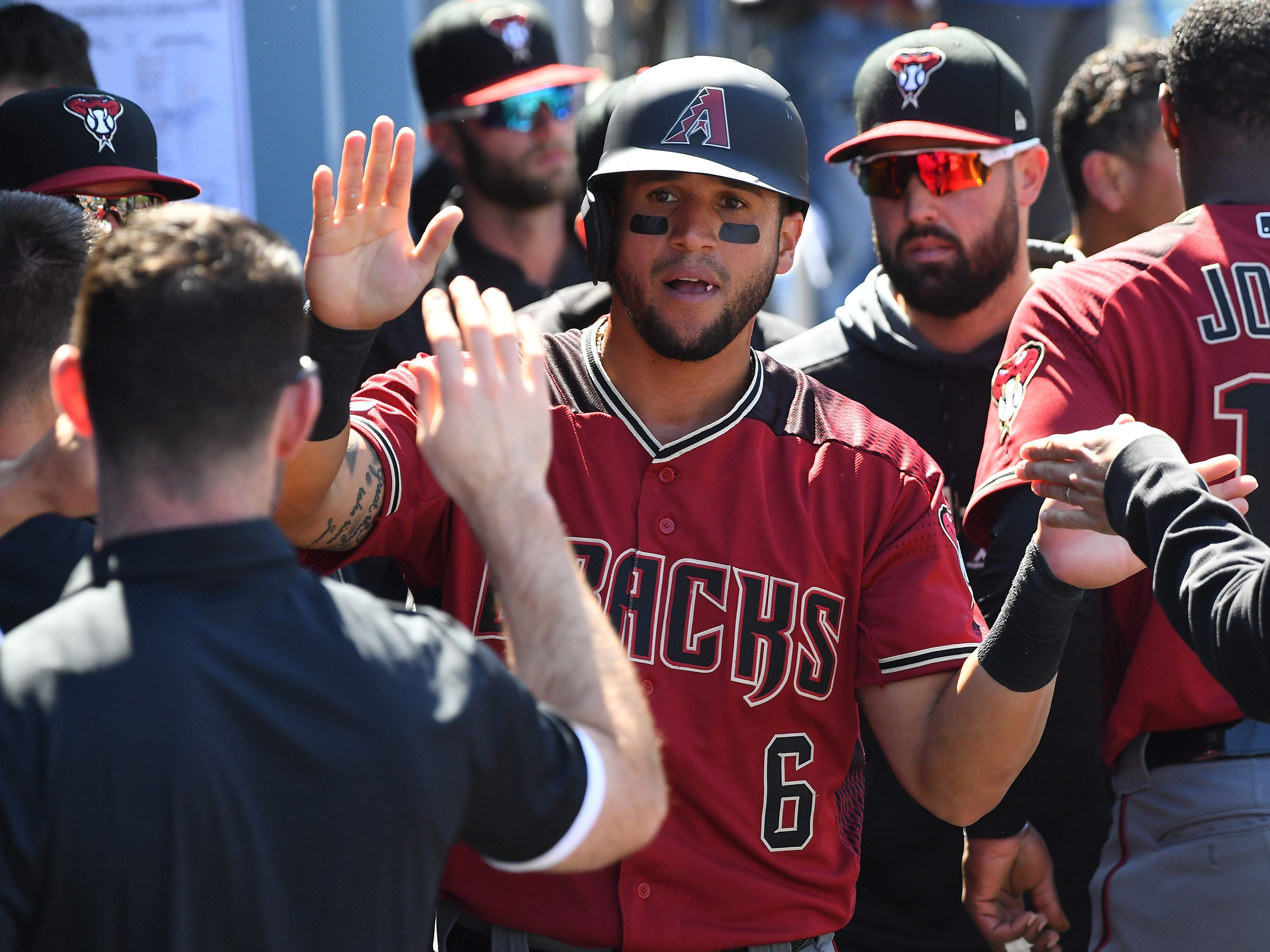 Mar 31, 2019; Los Angeles, CA, USA;    Arizona Diamondbacks right fielder David Peralta (6) is greeted in the dugout after scoring a run against the Los Angeles Dodgers in the fourth inning at Dodger Stadium.