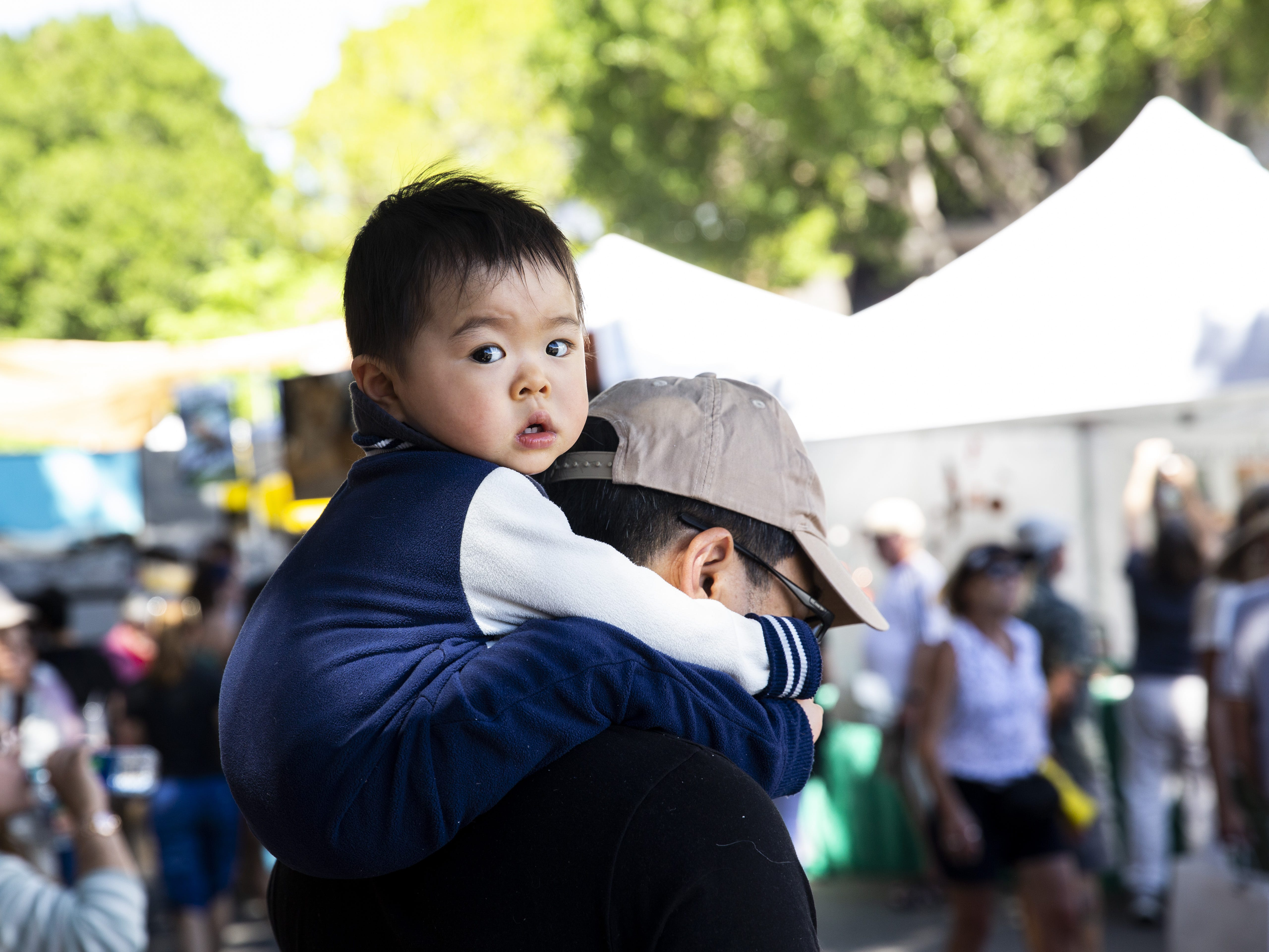 Trevor Wang, who is almost 1, clings to his father's neck at the Spring Tempe Festival of the Arts in downtown Tempe on March 30, 2019.