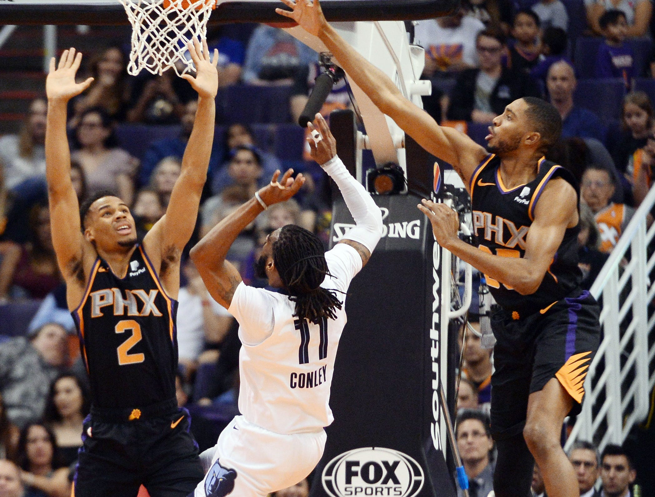 Mar 30, 2019; Phoenix, AZ, USA; Memphis Grizzlies guard Mike Conley (11) shoots over Phoenix Suns guard Elie Okobo (2) and Phoenix Suns forward Mikal Bridges (25) during the first half at Talking Stick Resort Arena. Mandatory Credit: Joe Camporeale-USA TODAY Sports