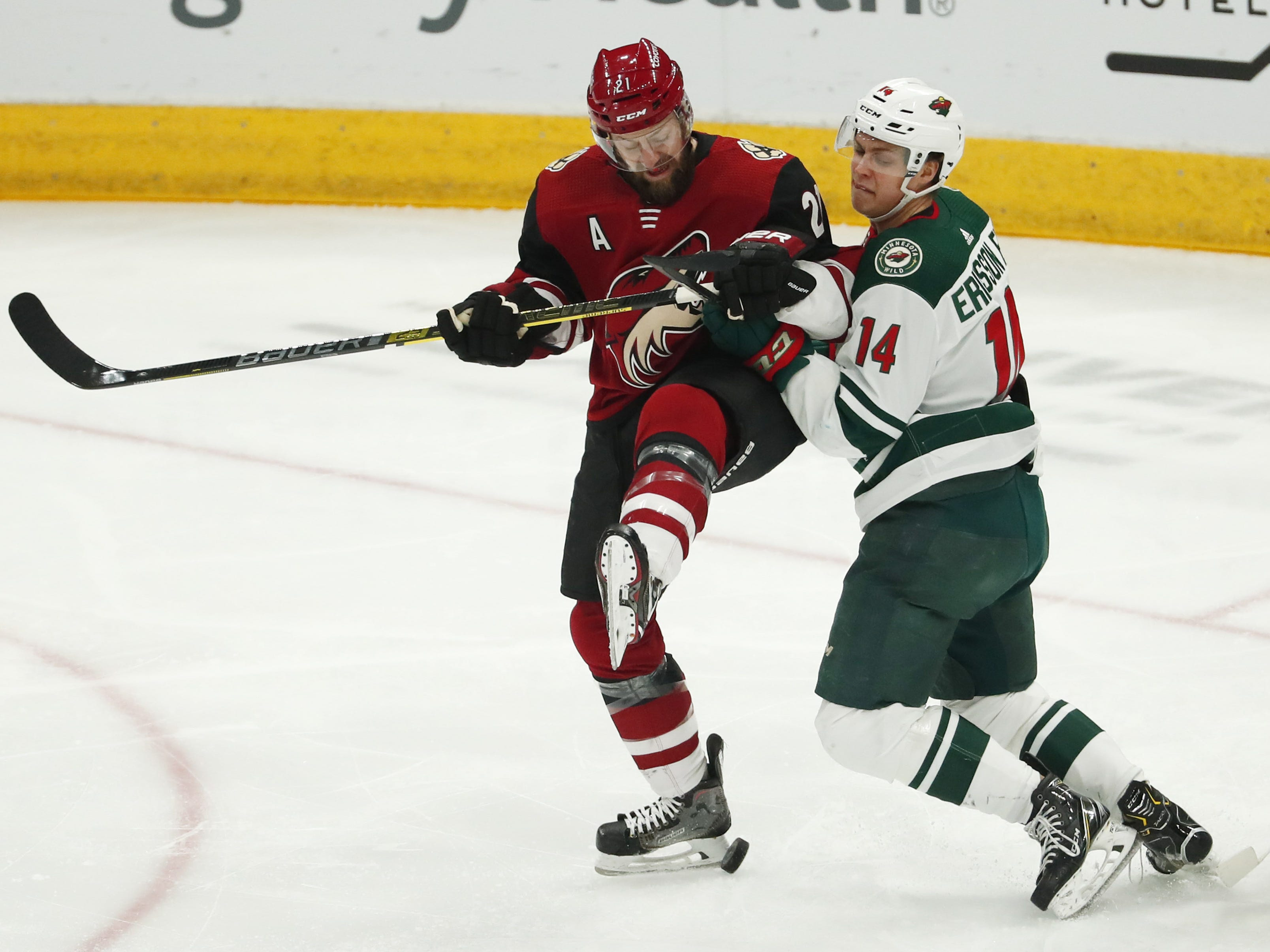Arizona Coyotes center Derek Stepan (21) is checked by Minnesota Wild center Joel Eriksson Ek (14) during the first period in Glendale March 31, 2019.