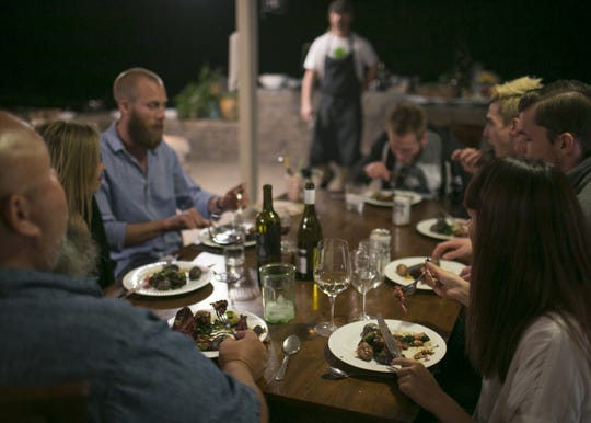 """A group of medical marijuana card holders and patients gathers to eat a """"medicated"""" St. Patrick's Day dinner cooked by cannabis cuisine chef Payton Curry in Scottsdale, Ariz. on March 17, 2018. The meal included five courses ranging from cannabis-infused salad dressing to cannabis-infused mustard over corned beef. Curry owns a cannabis cuisine company called Flourish that specializes in quality ingredients and affordable prices for medicated food."""