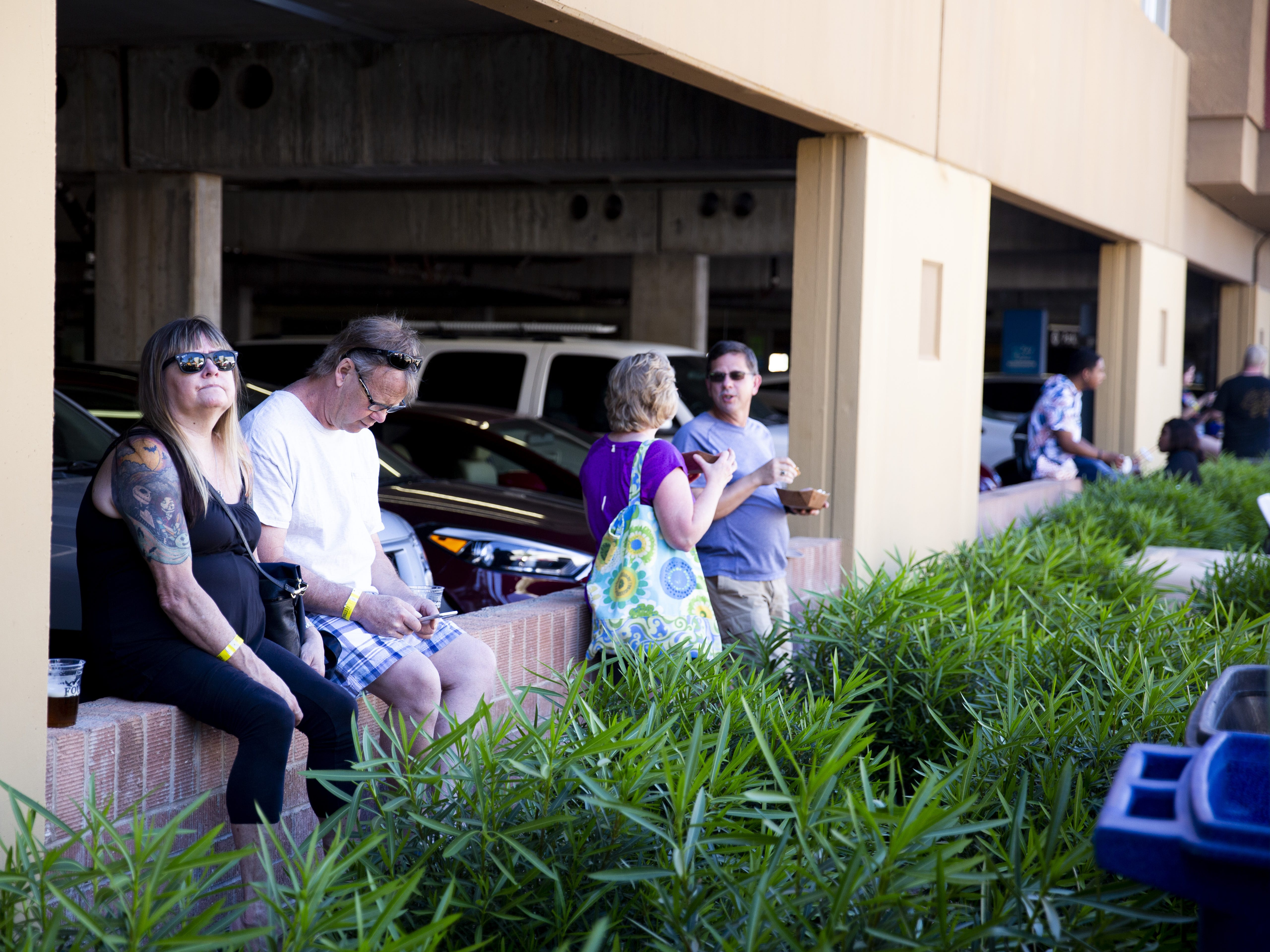 People perch on the edge of a parking garage wall to eat lunch from food trucks during the Spring Tempe Festival of the Arts in downtown Tempe on March 30, 2019.