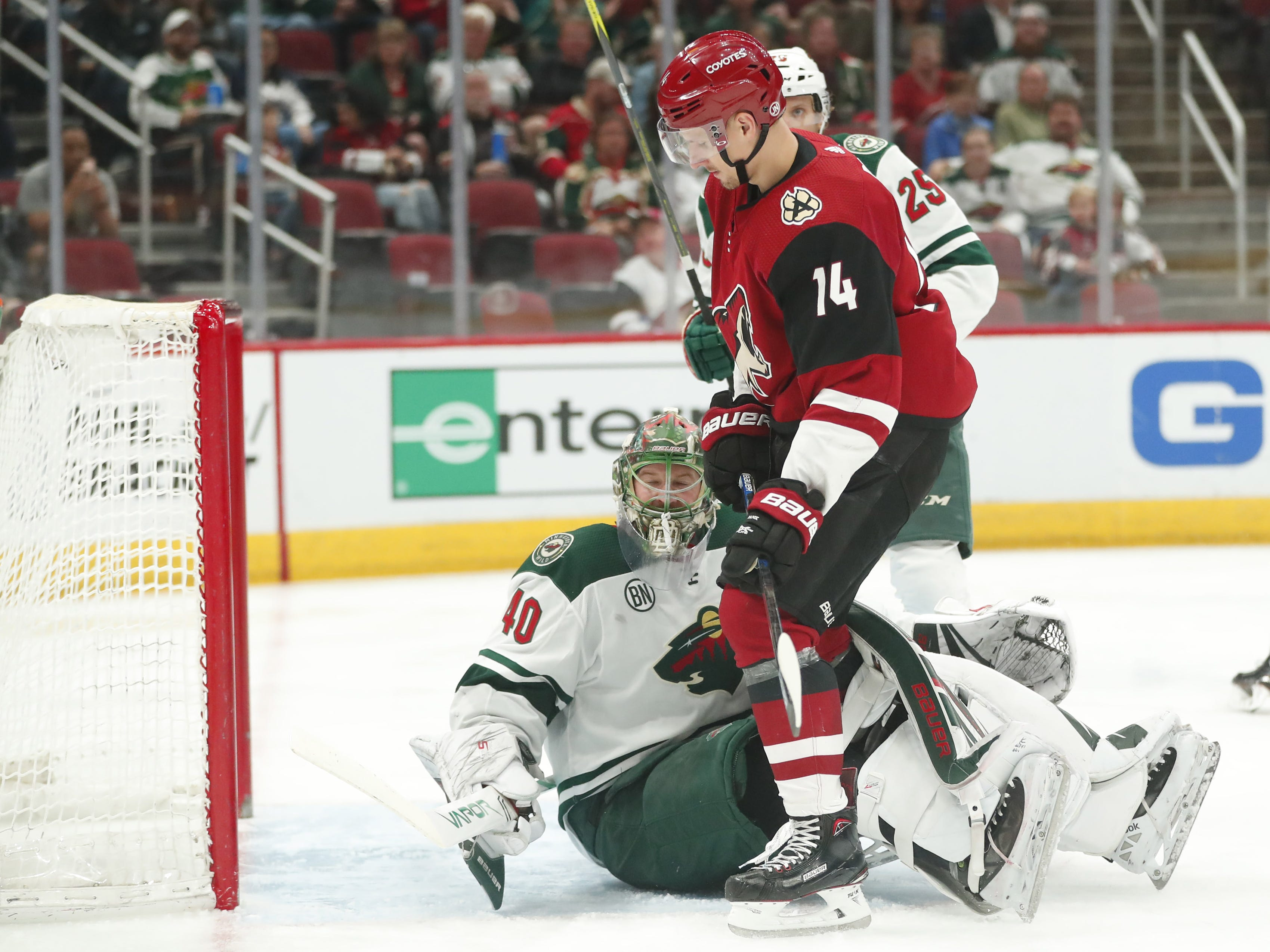 Arizona Coyotes right wing Richard Panik (14) gets tangled up with Minnesota Wild goaltender Devan Dubnyk (40) during the second period in Glendale March 31, 2019. Panik was called for goalie interference.