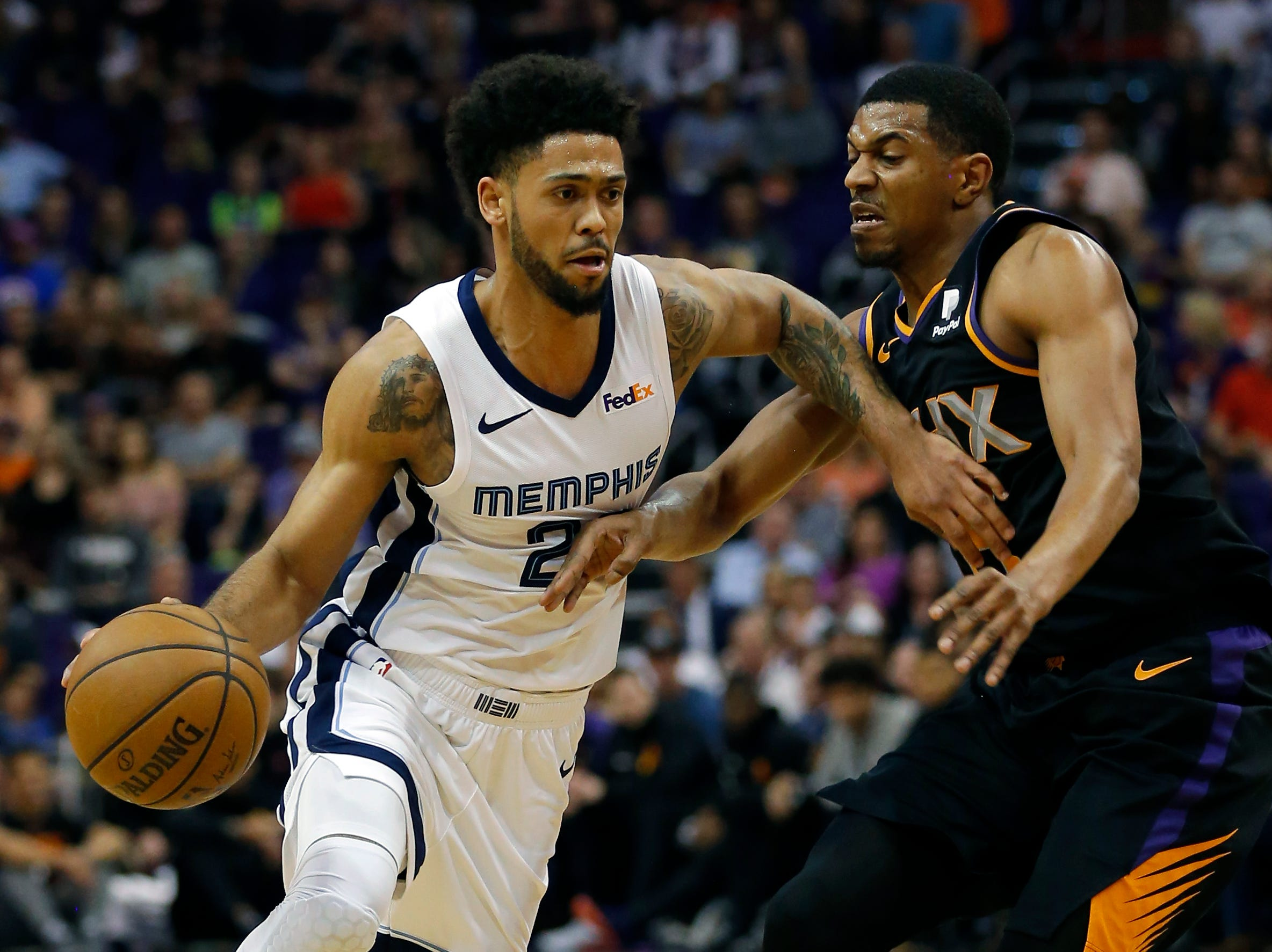 Memphis Grizzlies guard Tyler Dorsey, left, drives on Phoenix Suns guard De'Anthony Melton, right, in the first half during an NBA basketball game, Saturday, March 30, 2019, in Phoenix. (AP Photo/Rick Scuteri)
