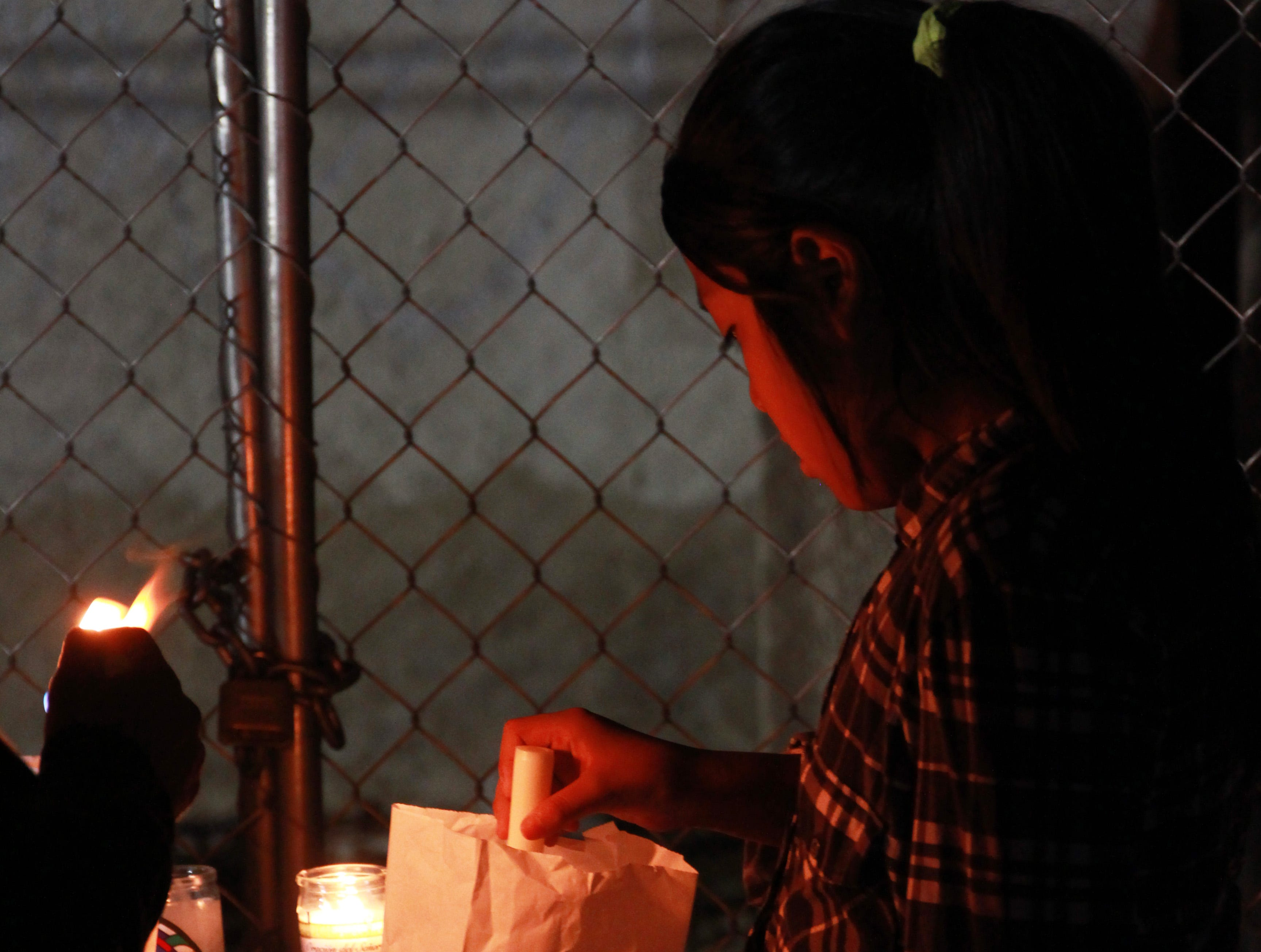 A young girl lights a candle in front of the burned-down church.