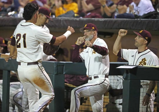 ASU's Carter Aldrete (21) bumps firsts with head coach Tracy Smith (center) and hitting coach Michael Earley (R) after scoring during the first inning against Arizona at Phoenix Municipal Stadium in Phoenix, Ariz. on March 30, 2019.