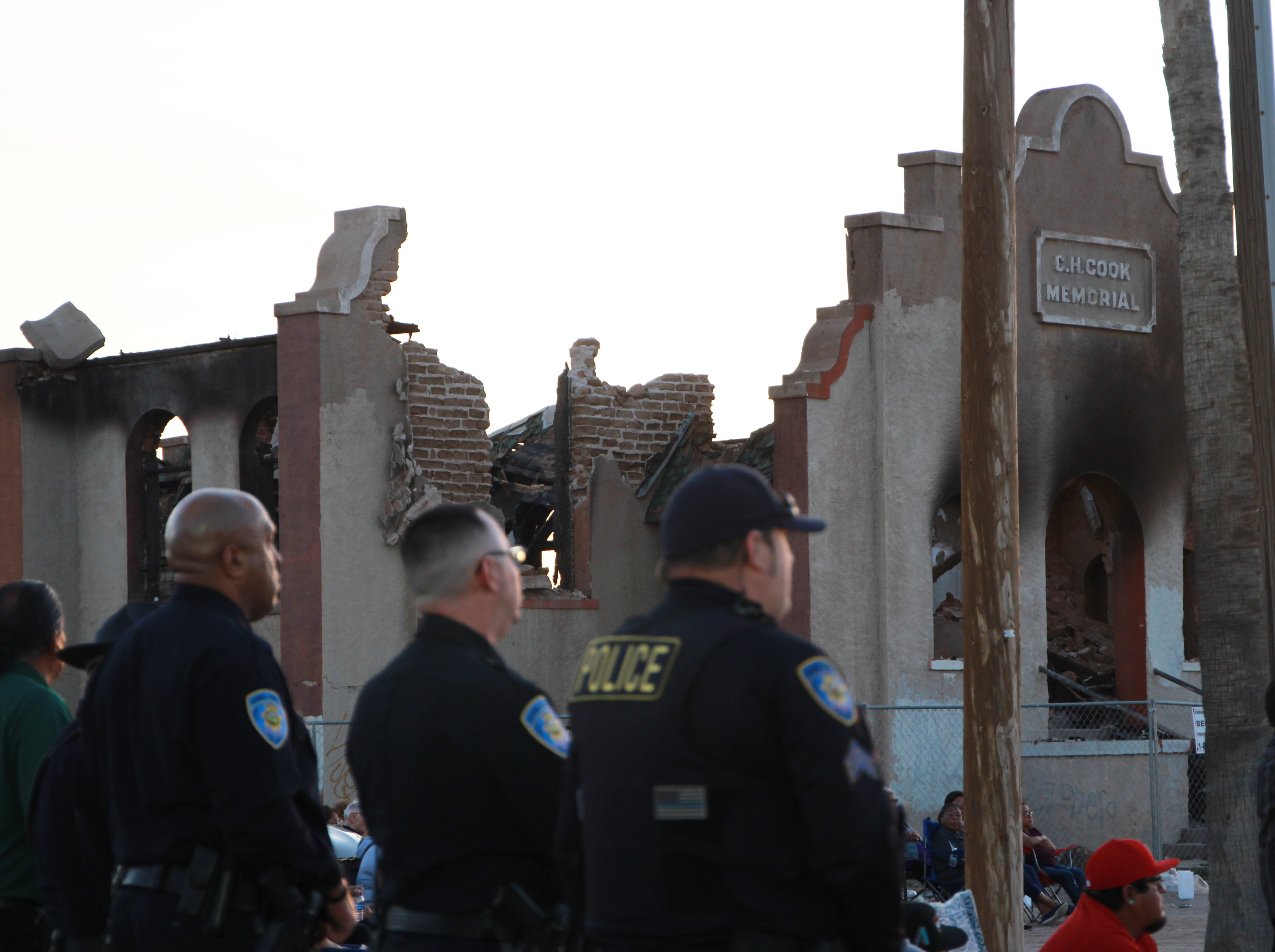 Policemen stand in front of the burned down church.
