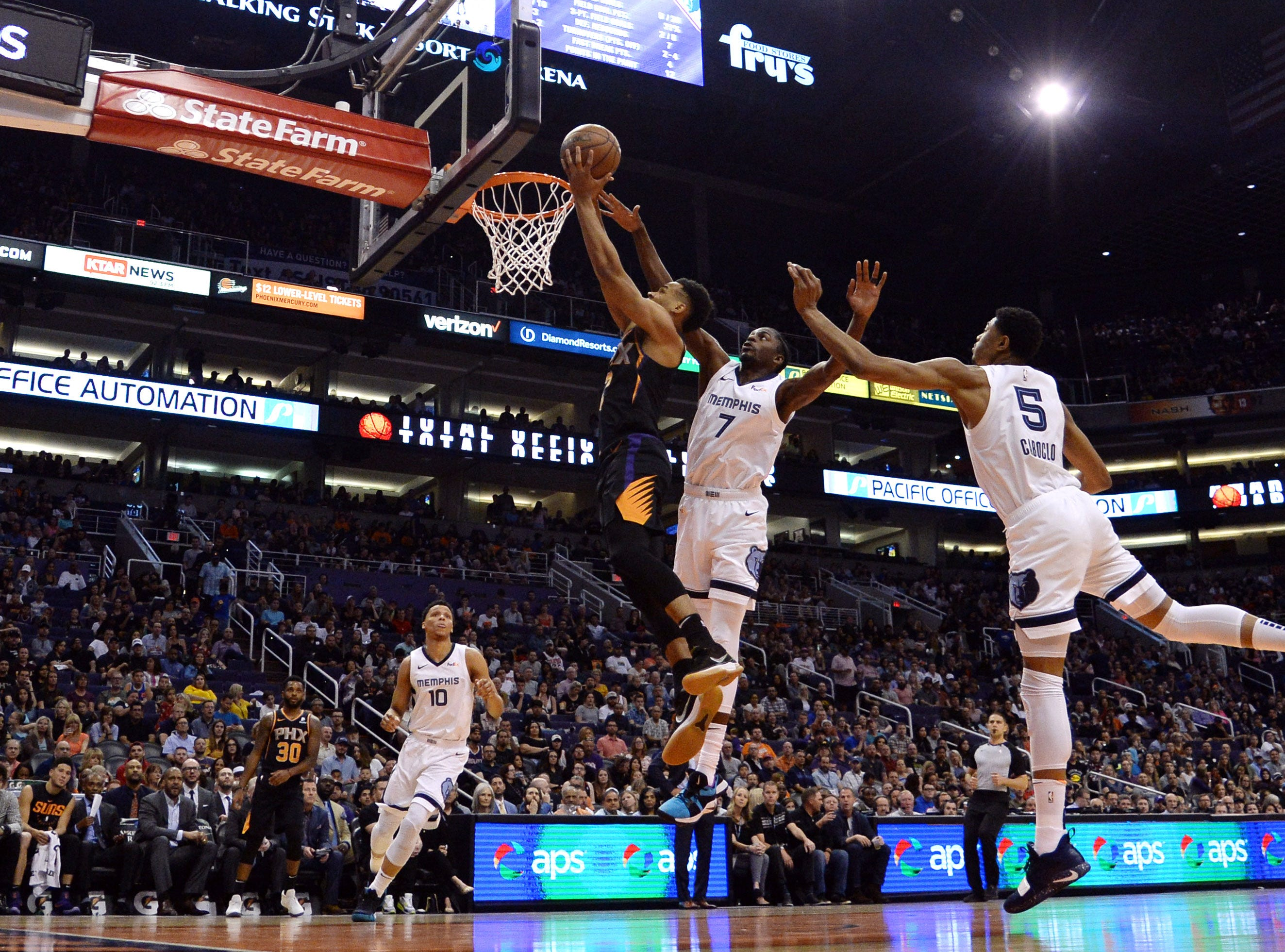 Mar 30, 2019; Phoenix, AZ, USA; Phoenix Suns guard Elie Okobo (2) goes up for a layup over Memphis Grizzlies forward Justin Holiday (7) and Memphis Grizzlies forward Bruno Caboclo (5) during the first half at Talking Stick Resort Arena. Mandatory Credit: Joe Camporeale-USA TODAY Sports