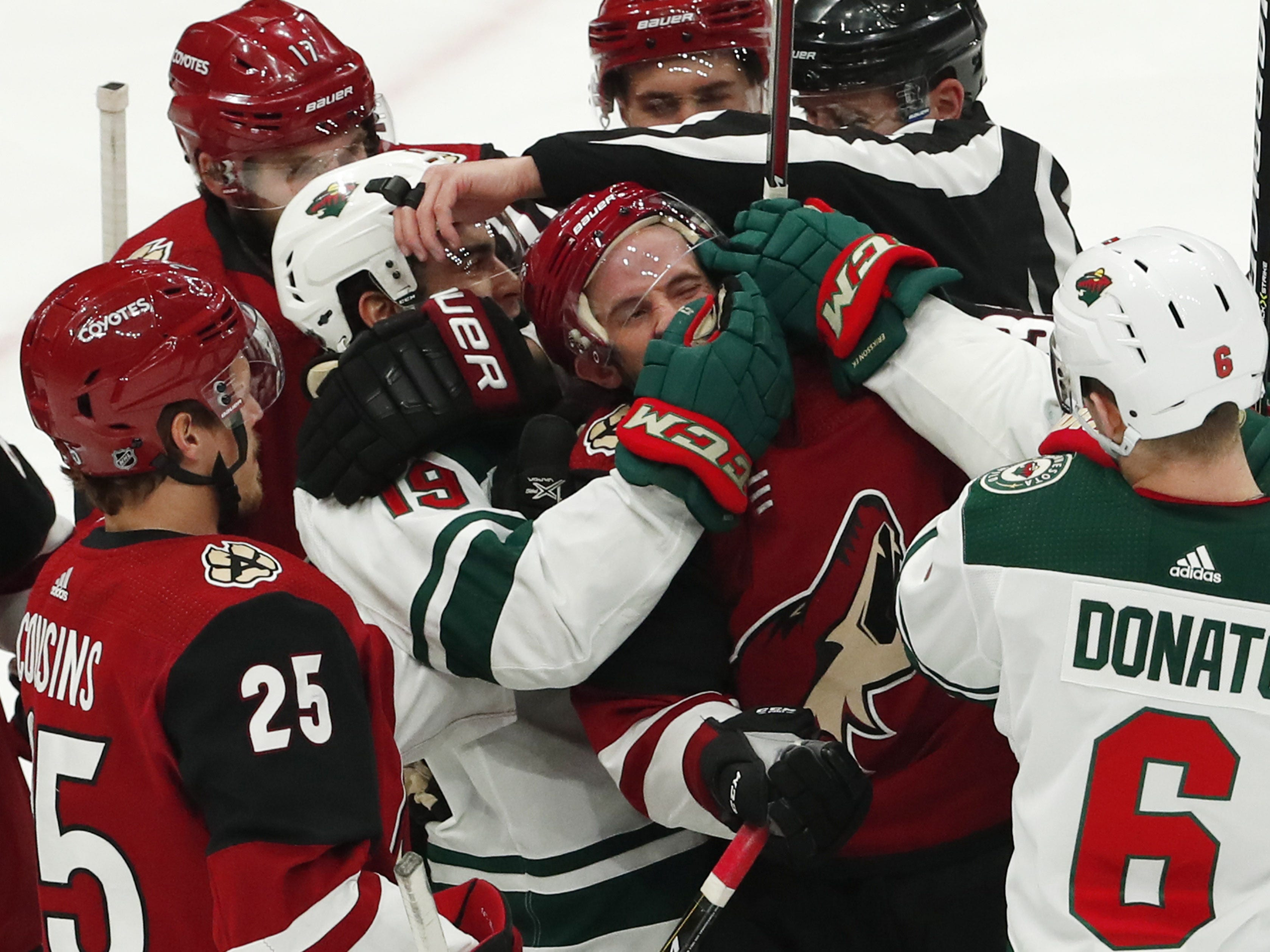 Arizona Coyotes defenseman Alex Goligoski (33) is held by Minnesota Wild center Luke Kunin (19) during the first period in Glendale March 31, 2019.