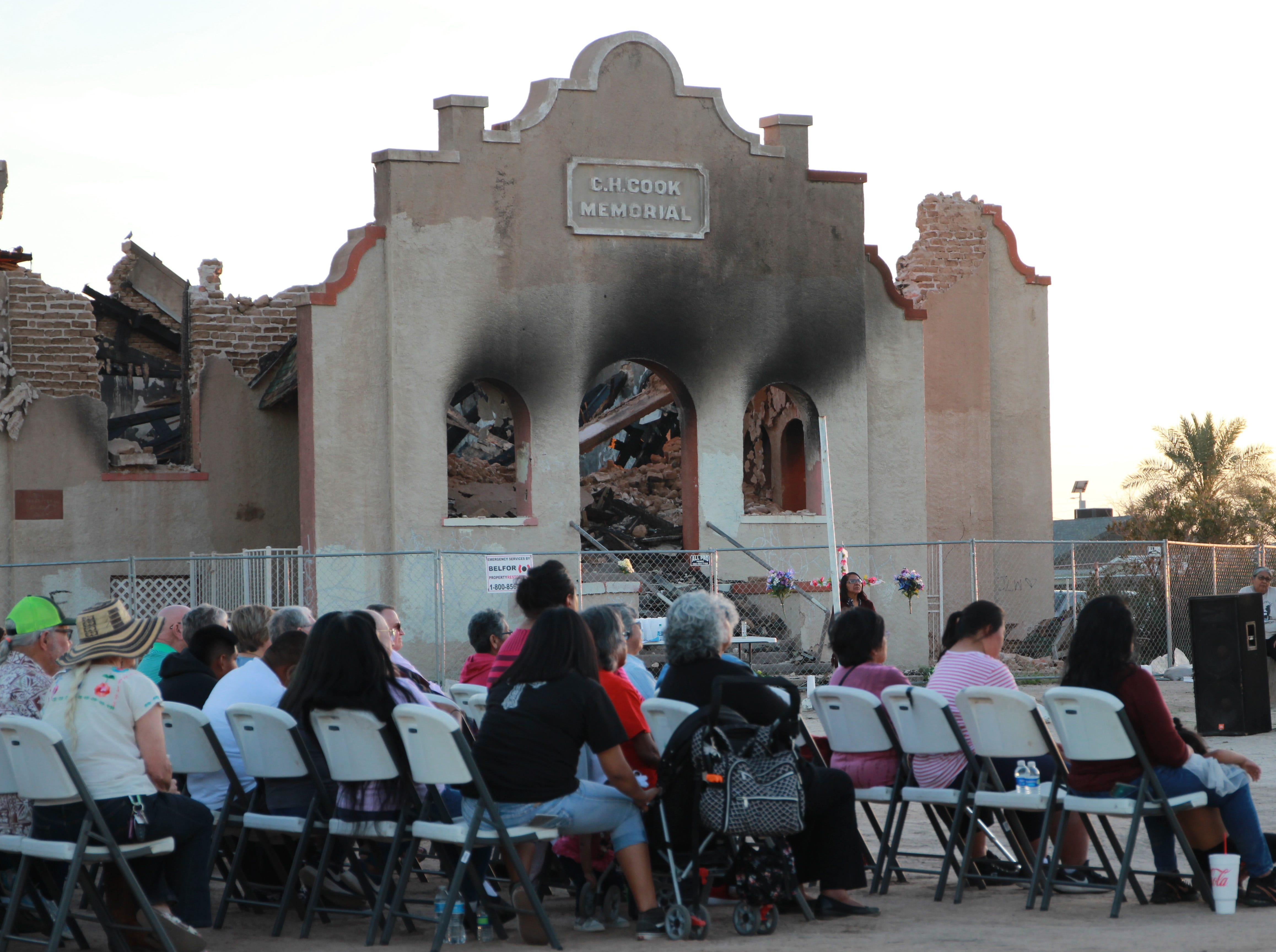 Members of the community sit in front of the church as they listen to stories and memories of the church.