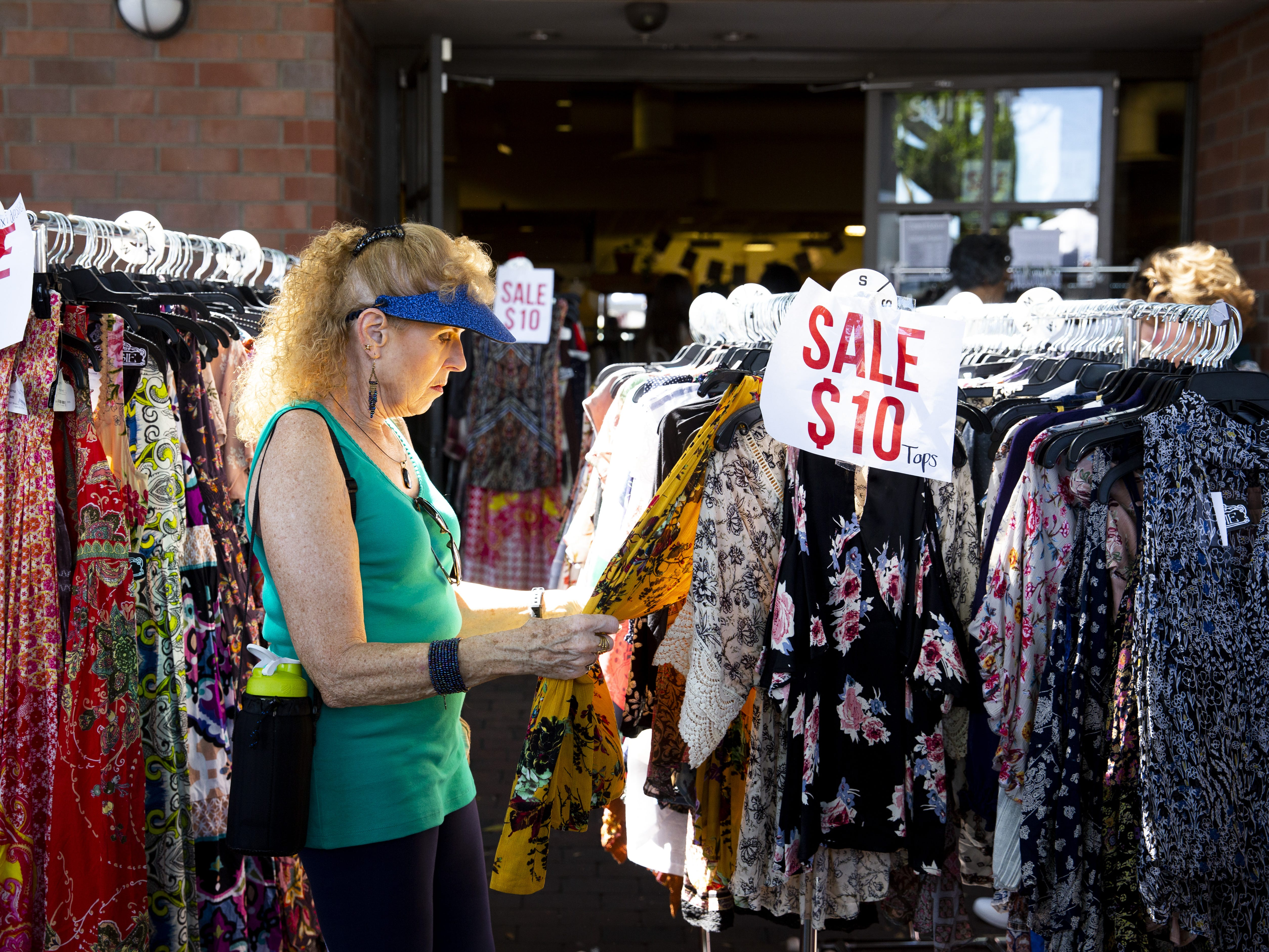 Rosie Mook, of Mesa, browses the shirts for sale at Creations Boutique on Mill Avenue during the Spring Tempe Festival of the Arts in downtown Tempe on March 30, 2019.