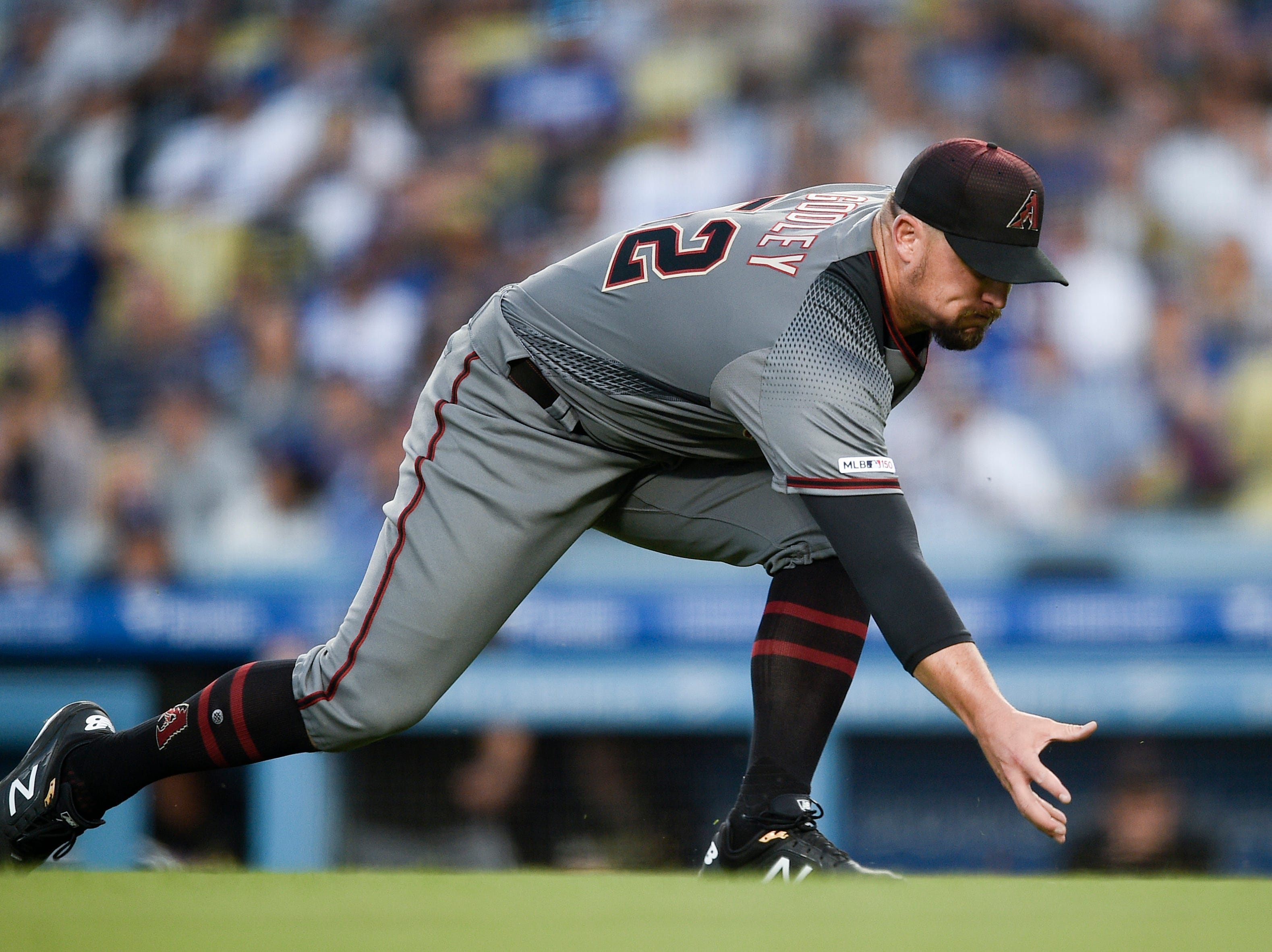 Mar 30, 2019; Los Angeles, CA, USA; Arizona Diamondbacks starting pitcher Zack Godley (52) fields a ball hit by Los Angeles Dodgers shortstop Corey Seager (not pictured) during the third inning at Dodger Stadium. Mandatory Credit: Kelvin Kuo-USA TODAY Sports