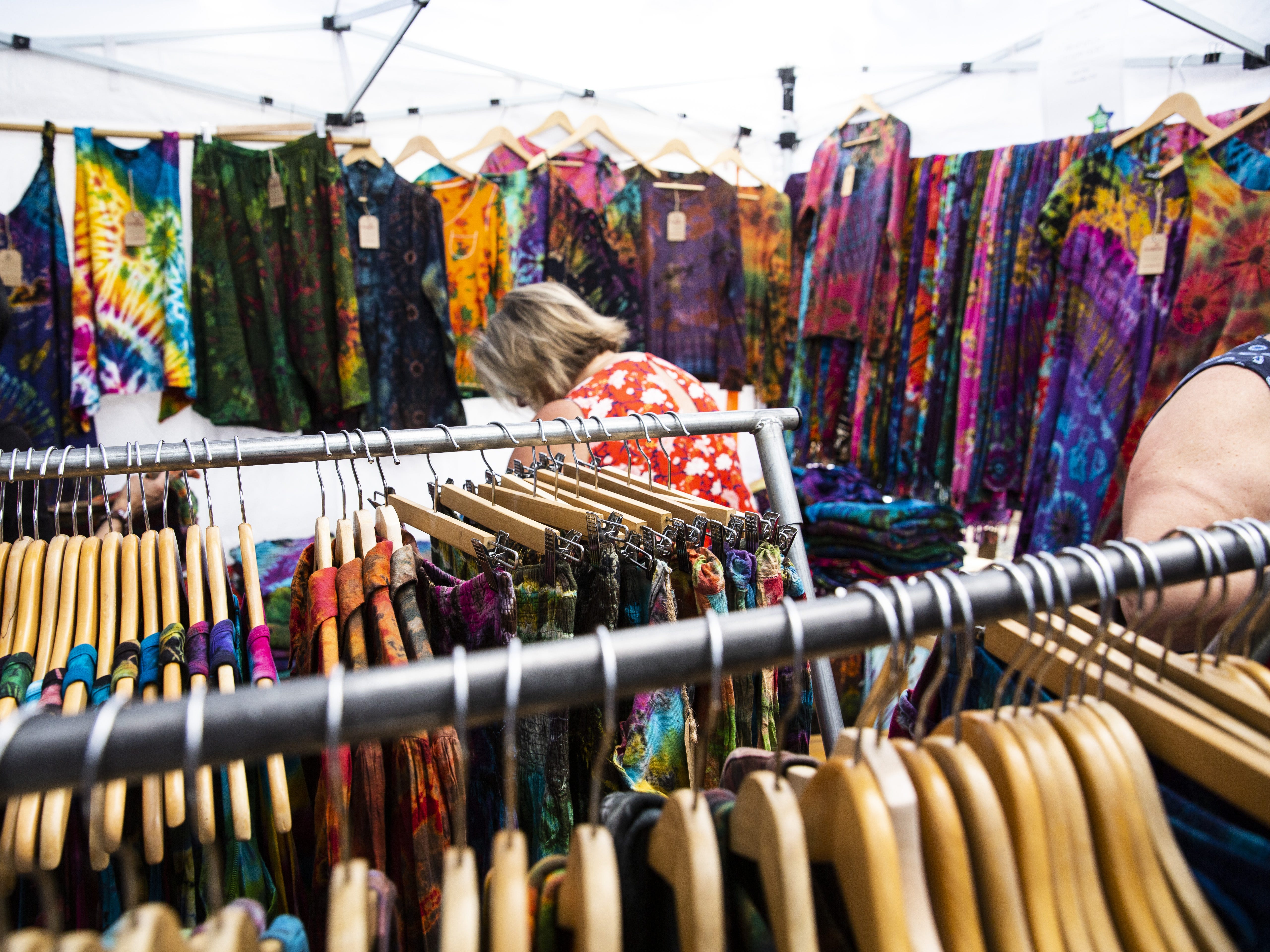 People shop for brightly colored clothes at the Spring Tempe Festival of the Arts on Saturday, March 30, 2019.