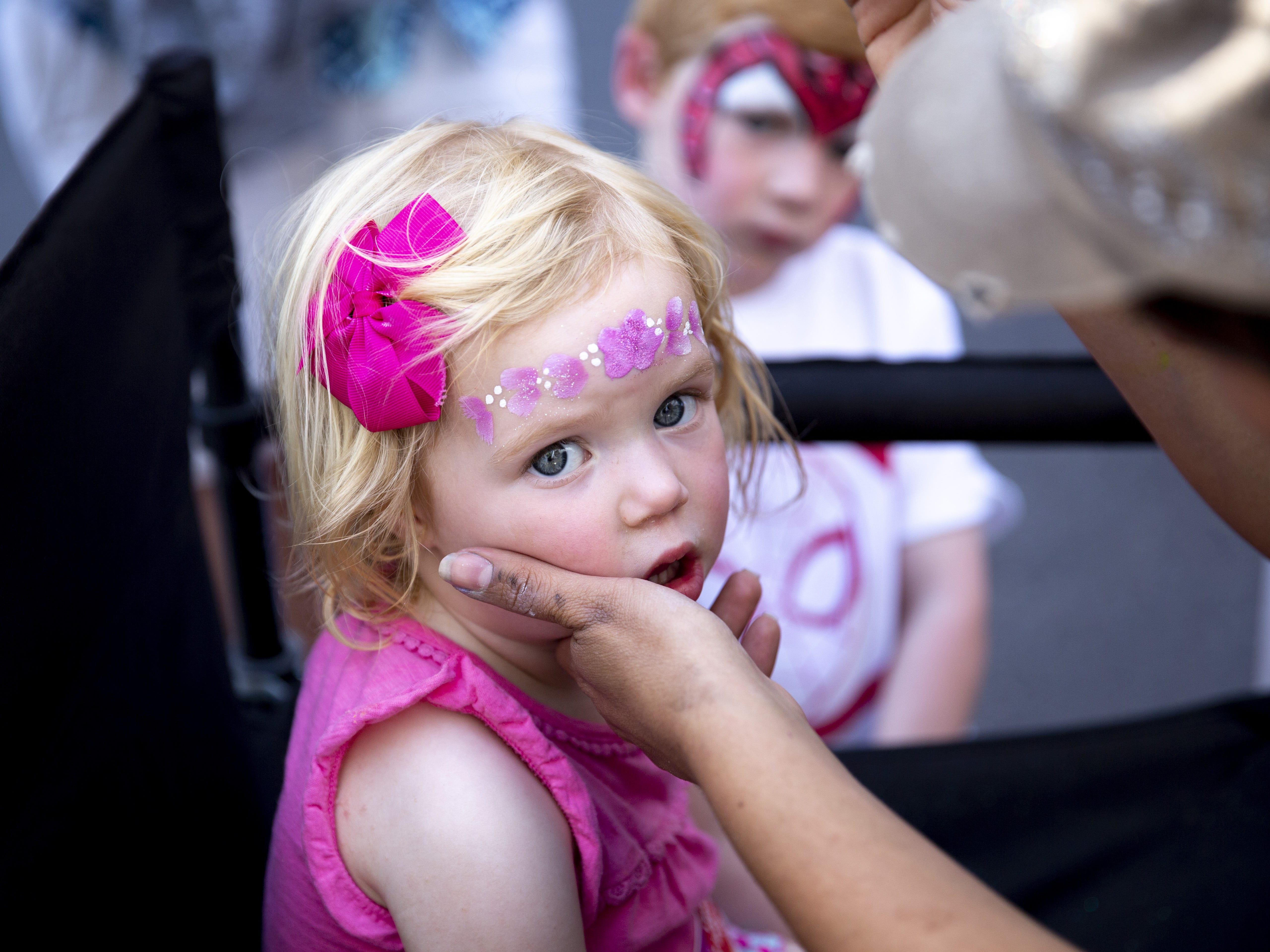 Harlow DeMeritt, 2, gets her face painted at the kids block, located between Fifth and Sixth Streets, during the Spring Tempe Festival of the Arts on Saturday, March 30, 2019.