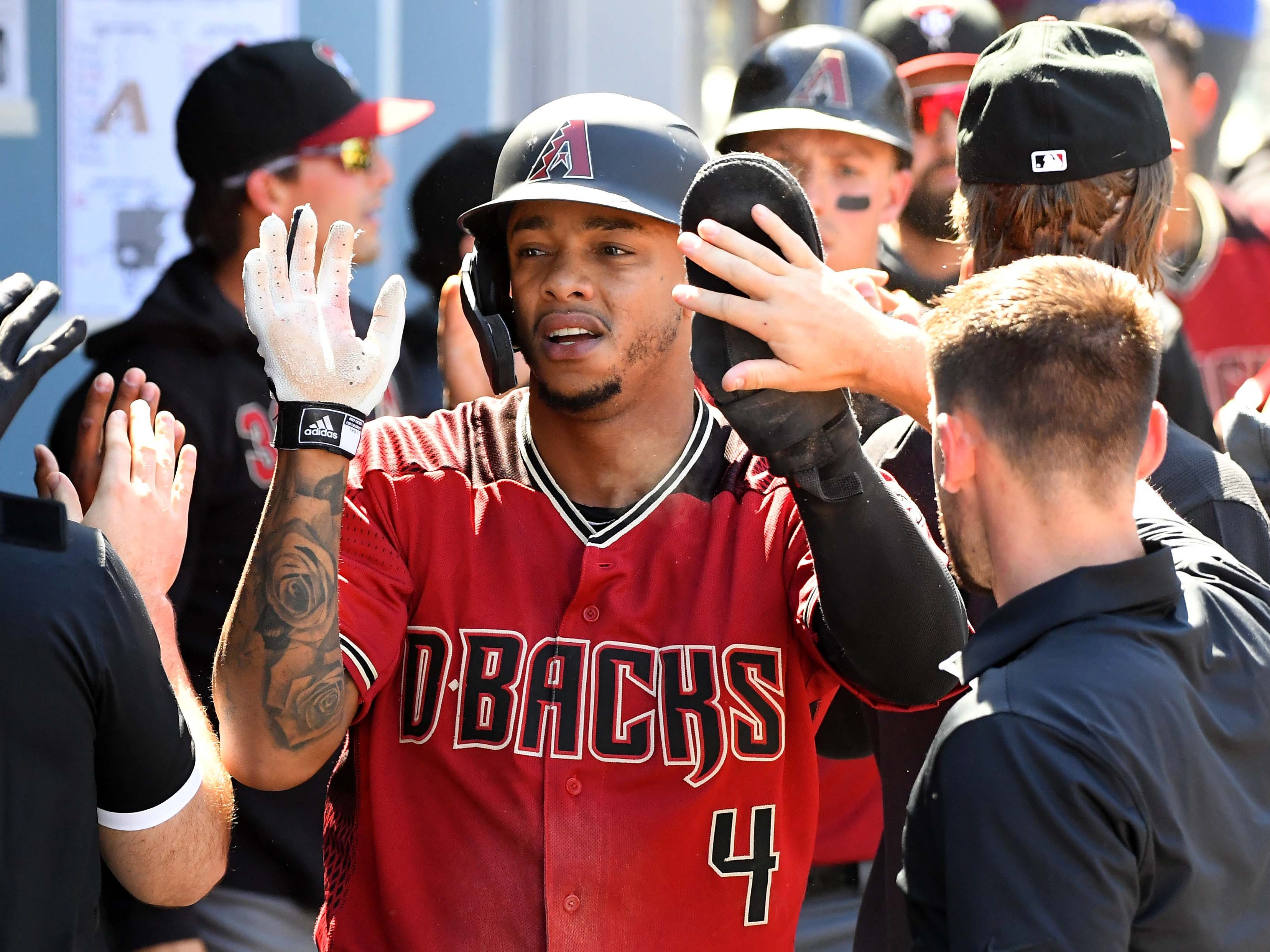 Mar 31, 2019; Los Angeles, CA, USA; Arizona Diamondbacks shortstop Ketel Marte (4) is greeted in the dugout after scoring a run in the fourth inning of the game at Dodger Stadium.