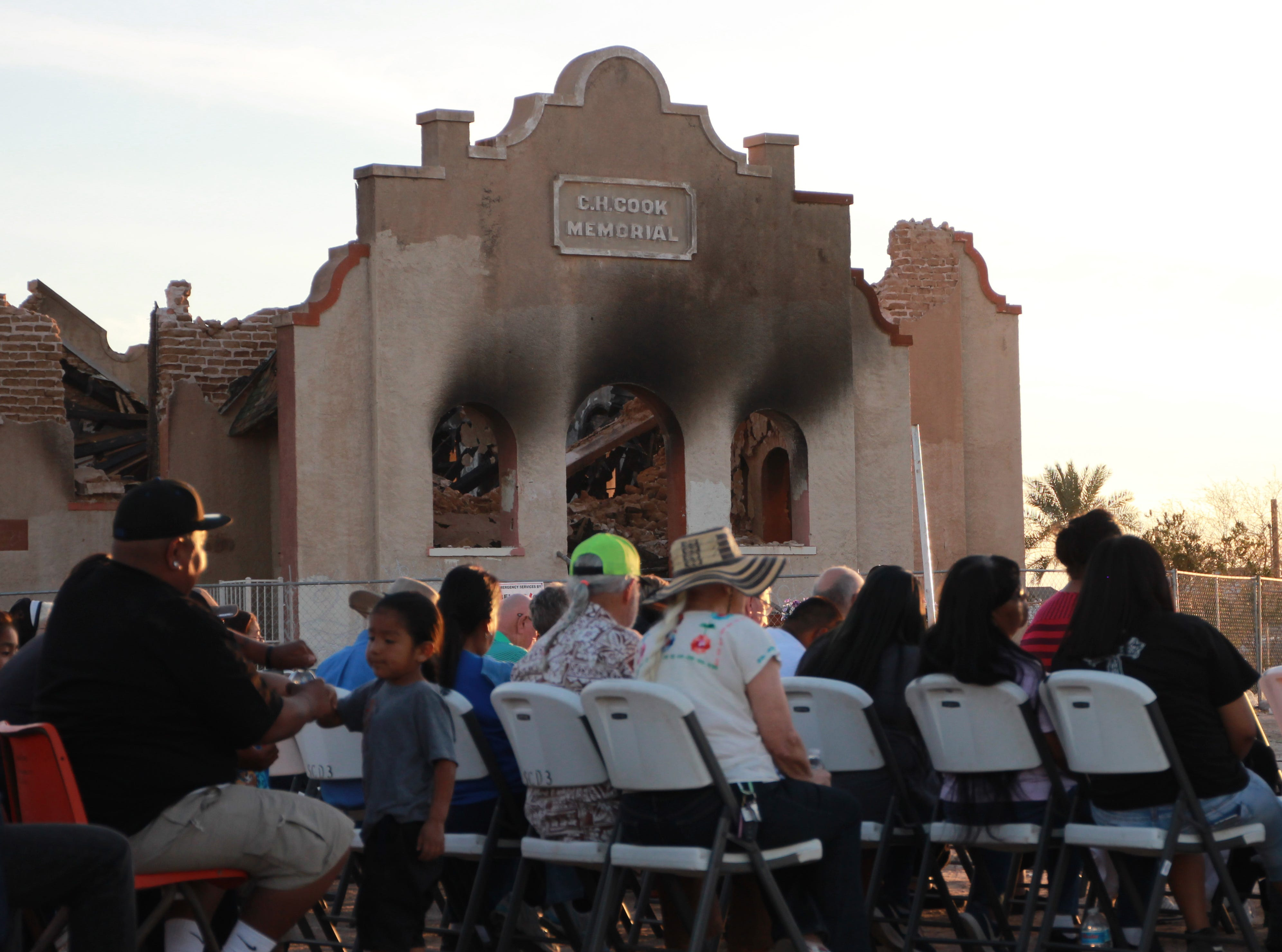 The burned-down church looms over the crowd Friday evening during the vigil.