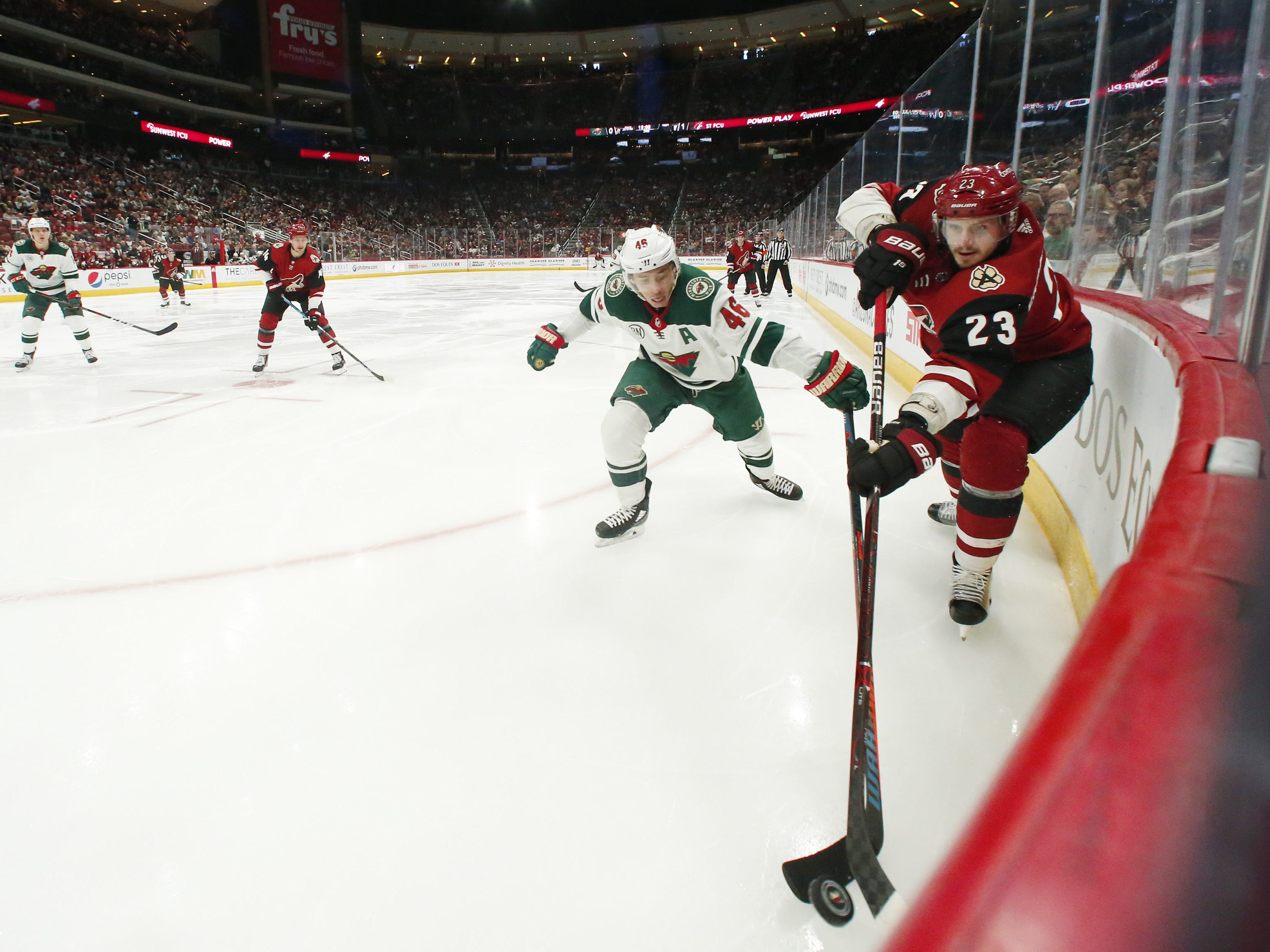 Arizona Coyotes defenseman Oliver Ekman-Larsson (23) works the puck away from Minnesota Wild defenseman Jared Spurgeon (46) during the second period in Glendale March 31, 2019.