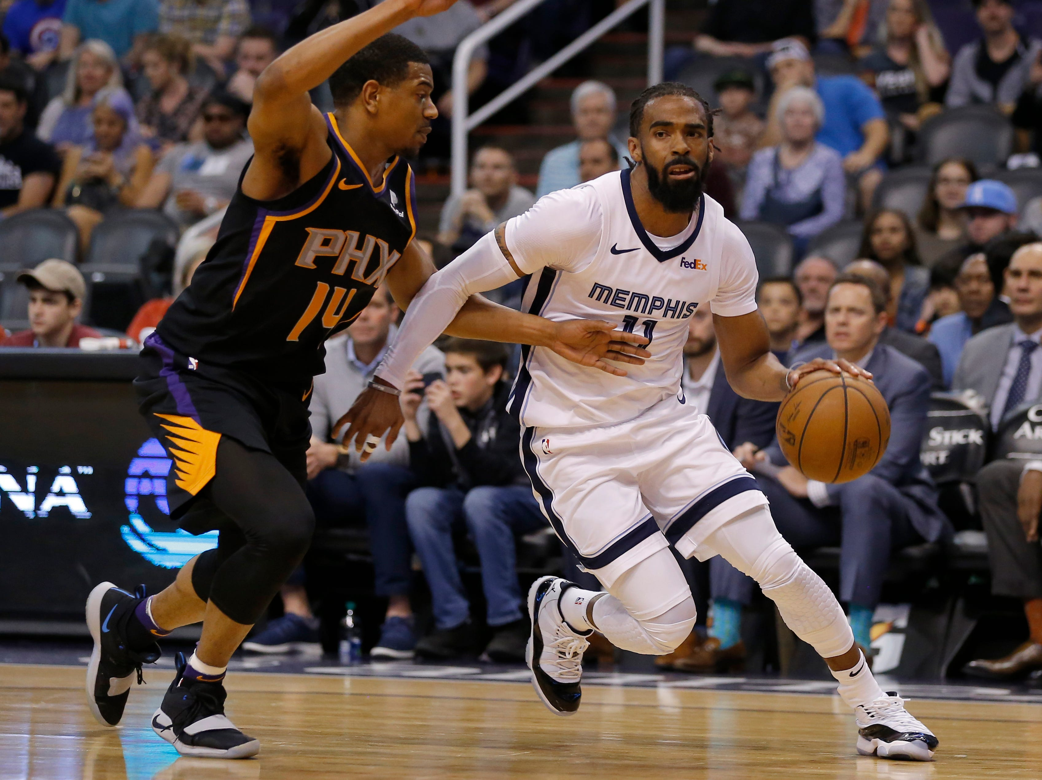 Memphis Grizzlies guard Mike Conley, right, drives past Phoenix Suns guard De'Anthony Melton, left, in the first half during an NBA basketball game, Saturday, March 30, 2019, in Phoenix. (AP Photo/Rick Scuteri)