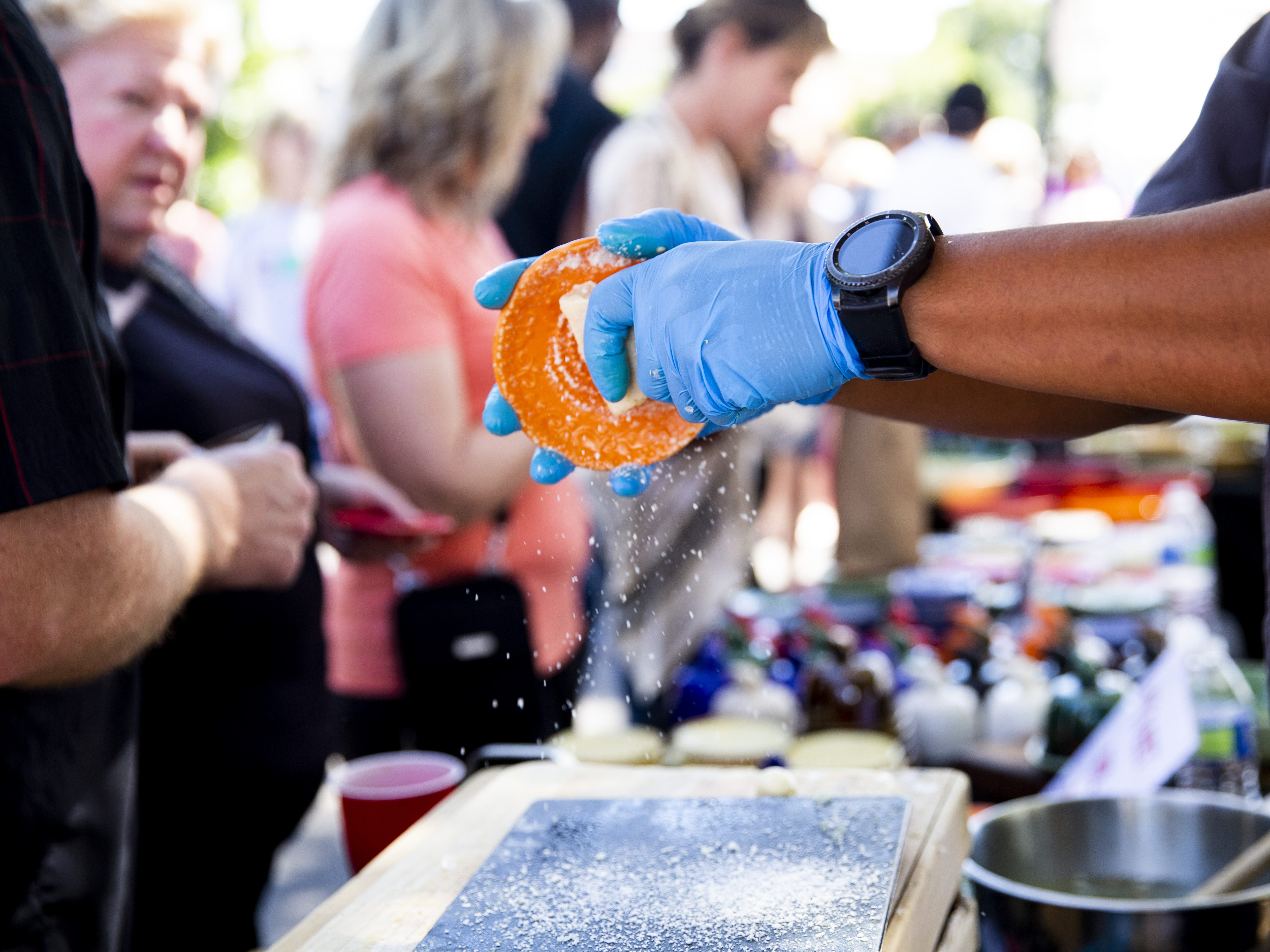 Patrick Lauterio, the owner of Pako Lazo Pottery, demonstrates how his dishes can be used to grate cheese during the Spring Tempe Festival of the Arts in downtown Tempe on March 30, 2019.