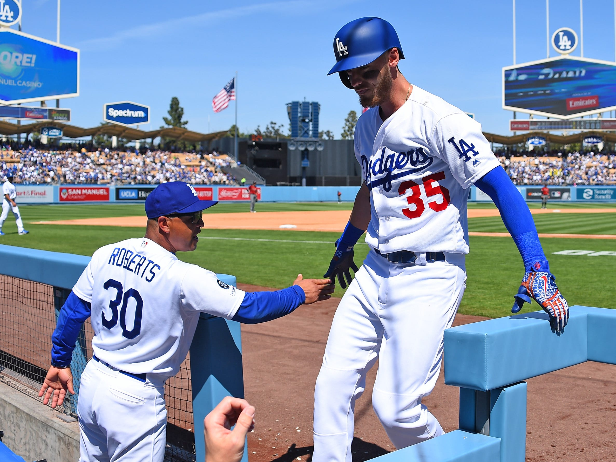 Mar 31, 2019; Los Angeles, CA, USA; Los Angeles Dodgers center fielder Cody Bellinger (35) is greeted in the dugout by manager Dave Roberts (30) after hitting a solo home run in the third inning against the Arizona Diamondbacks at Dodger Stadium.