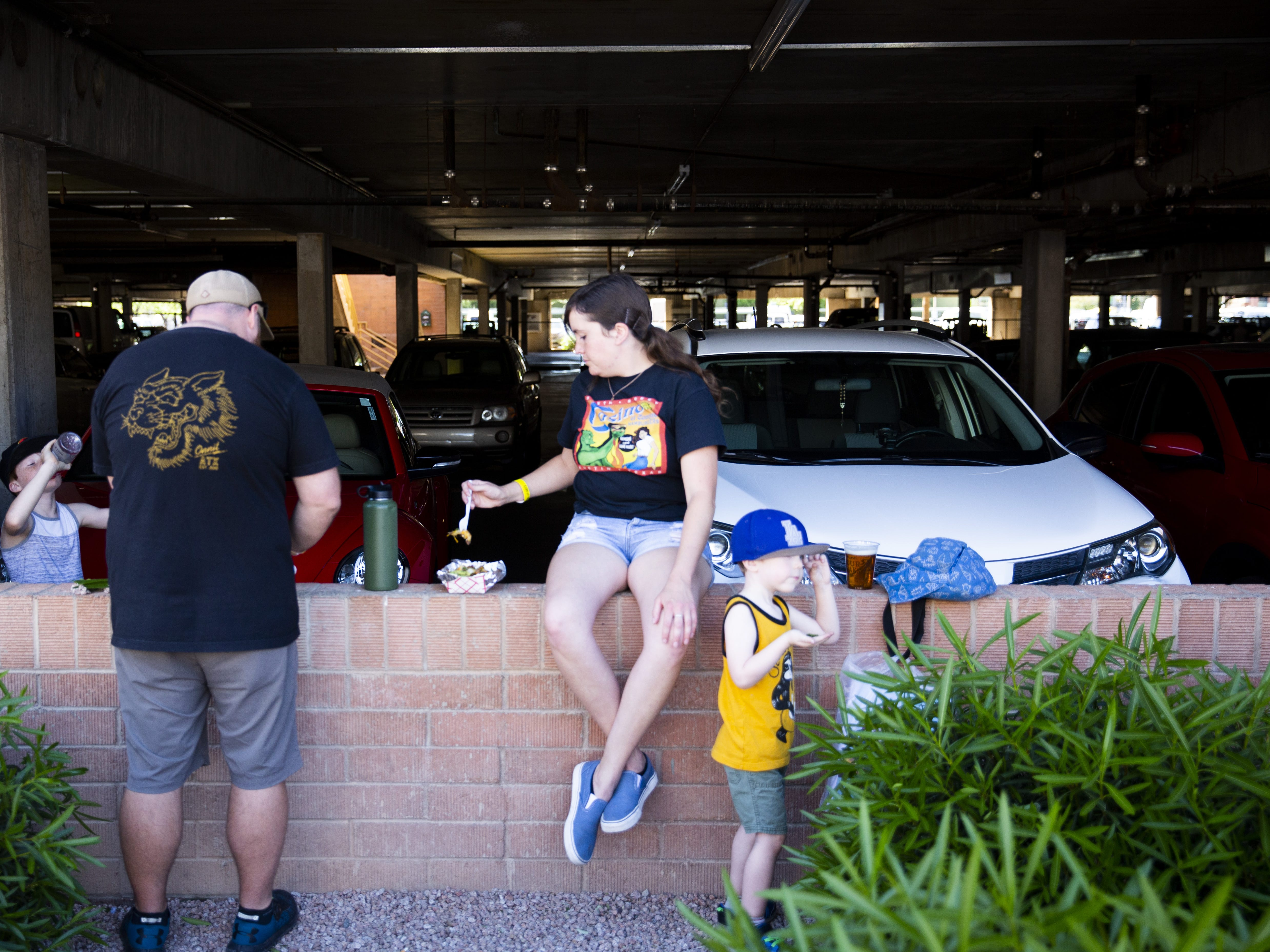 A family sits on the edge of a parking garage to eat lunch during the Spring Tempe Festival of the Arts in downtown Tempe on March 30, 2019.