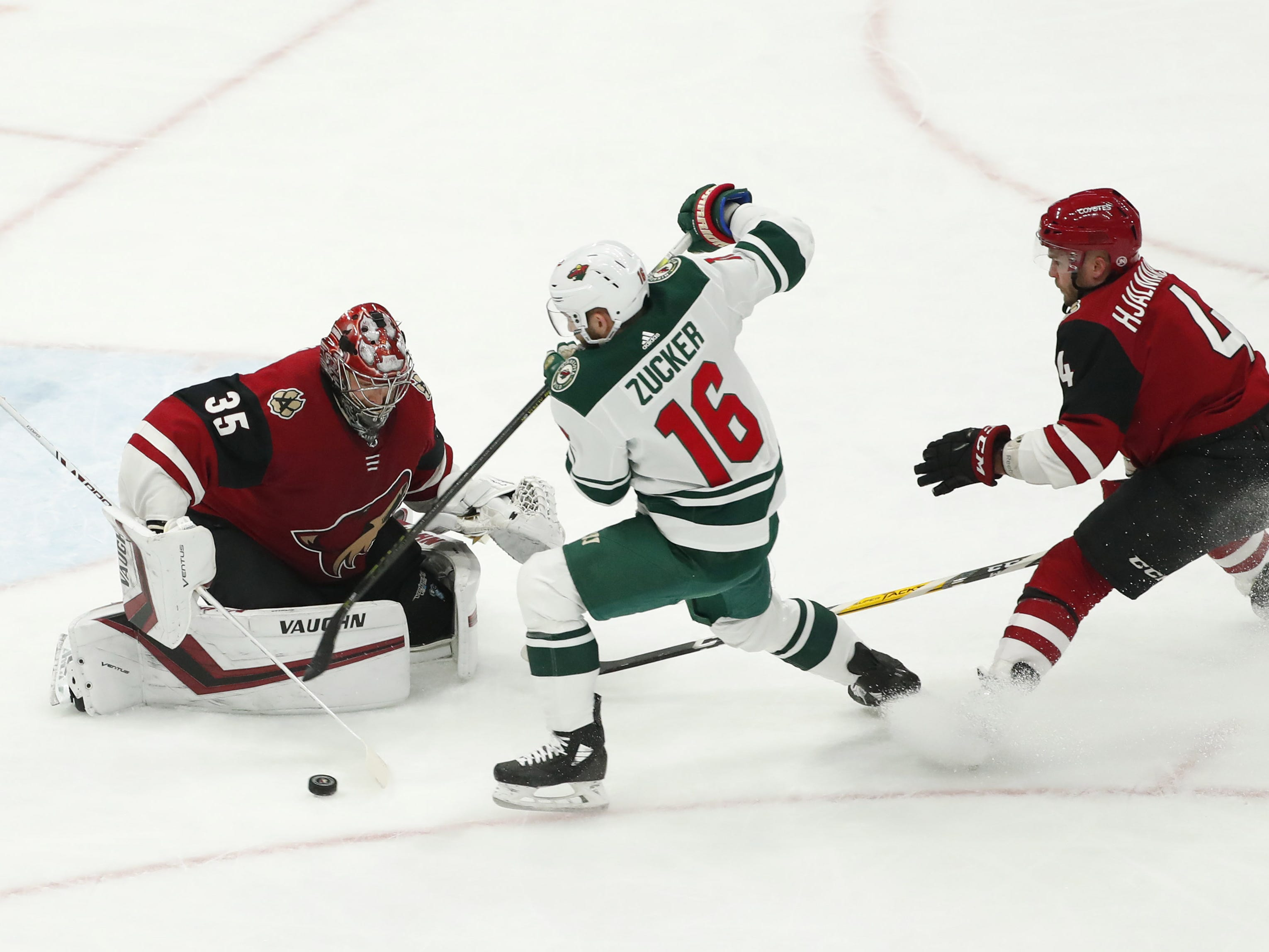 Arizona Coyotes goaltender Darcy Kuemper (35) blocks a shot by Minnesota Wild left wing Jason Zucker (16) as defenseman Niklas Hjalmarsson (4) defends during the first period in Glendale March 31, 2019. Hjalmarsson was called for slashing.