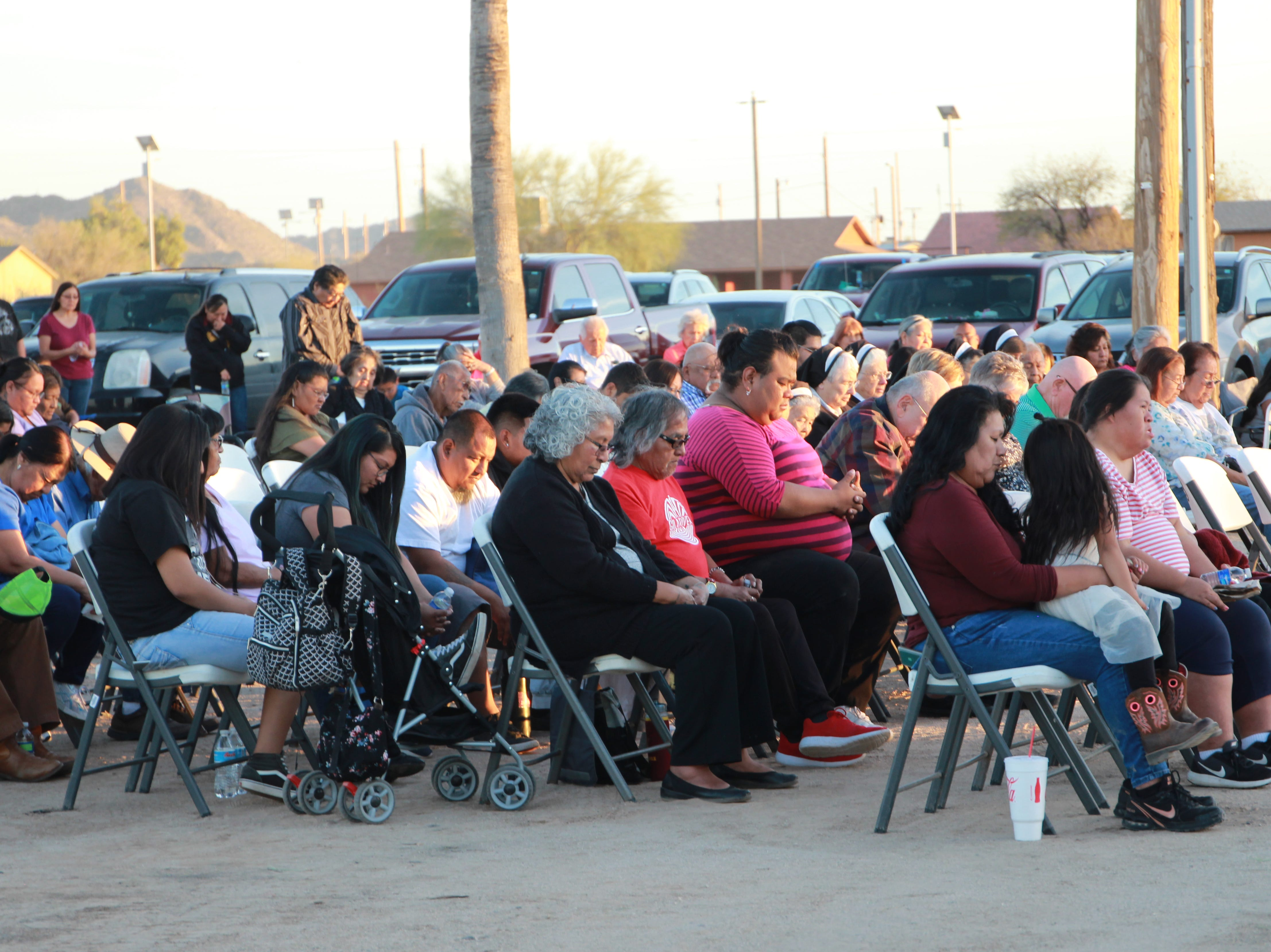 Members of the community pray during the vigil on Friday evening.