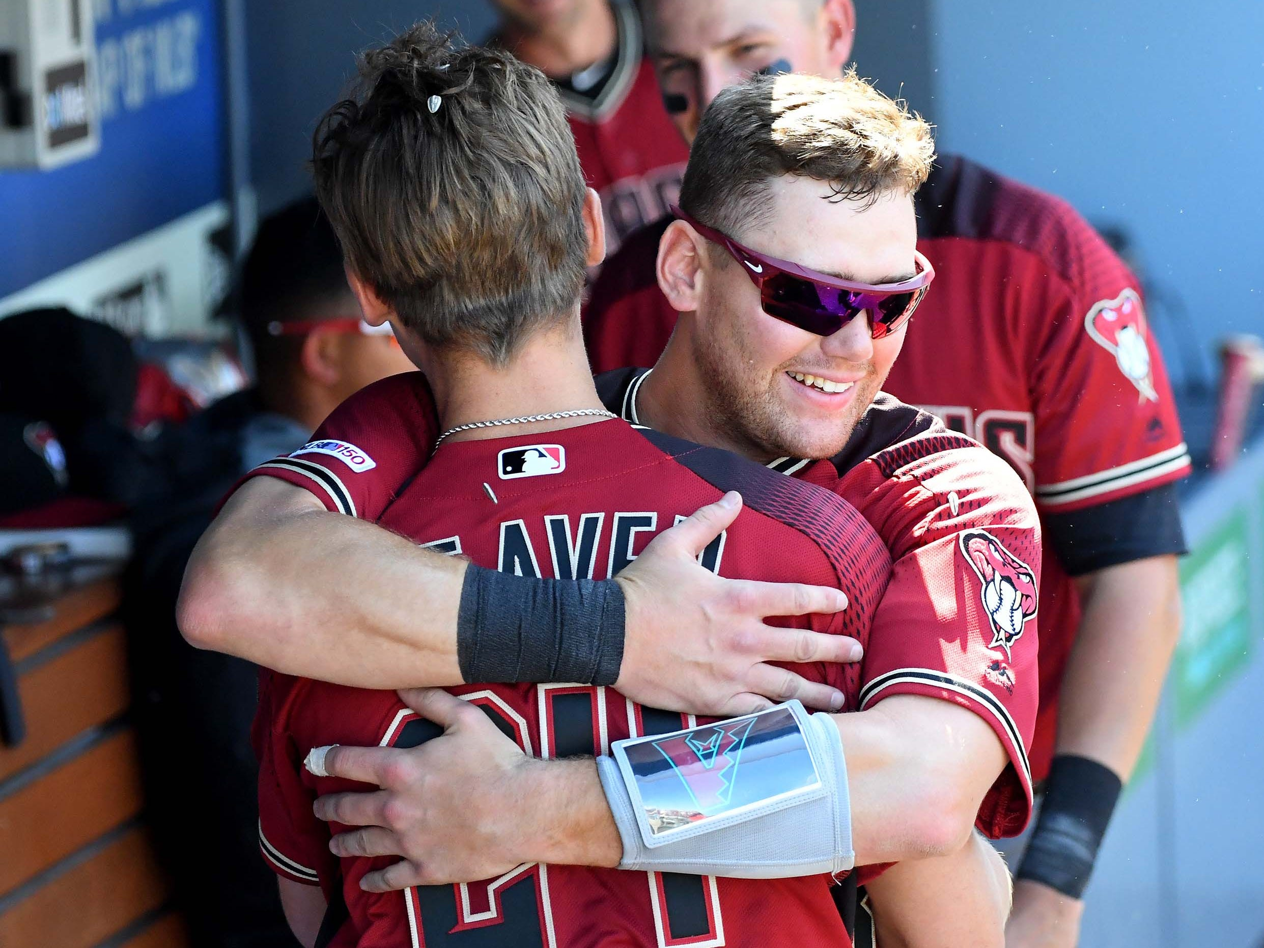 Mar 31, 2019; Los Angeles, CA, USA; Arizona Diamondbacks starting pitcher Luke Weaver (24)  gets a hug from Arizona Diamondbacks catcher Carson Kelly (18) in the dugout after hitting a solo home run in the fourth inning of the game at Dodger Stadium.